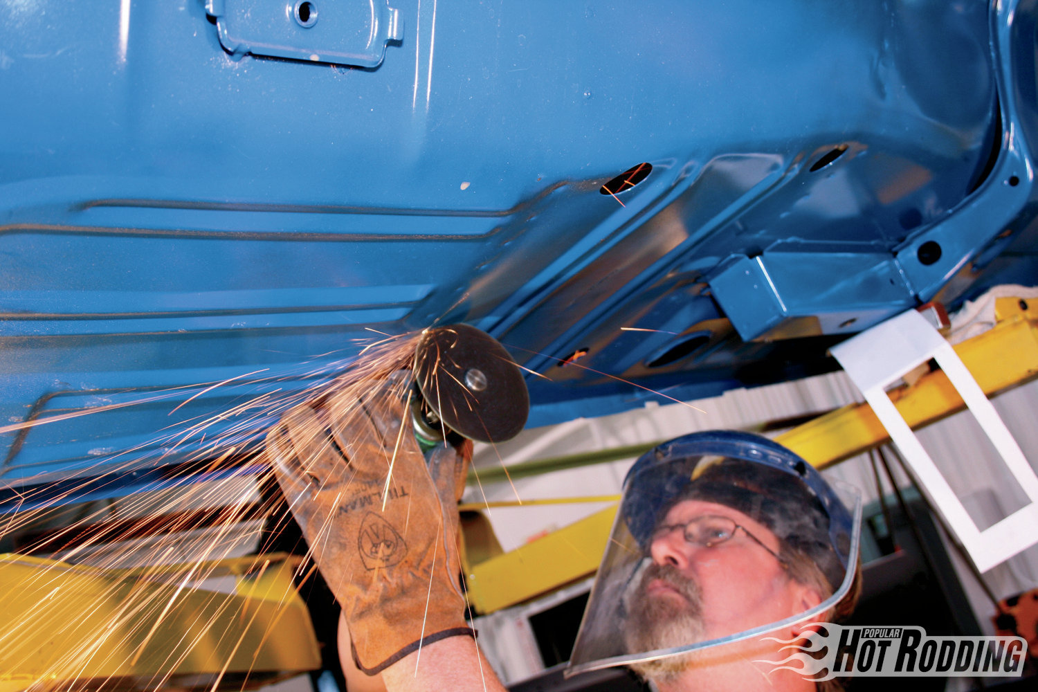 5. Cut the floorpan along the lines using a cutoff wheel. To prepare the floor for welding, remove paint from around the edges of the cutout area using a grinder. Strip the front subframe down to bare metal as well.