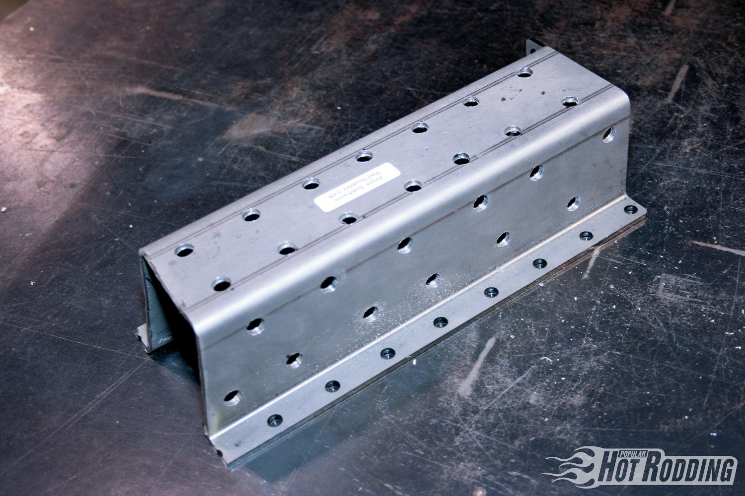 8. To prep the reinforcement plates for plug-welding, drill ⅜-inch holes spaced 1-inch apart along the bottom and sides of the plate. This will net 12-14 plug weld holes on each flat section of the plate. Deburr any sharp edges, then spray the plate down with weld-thru primer to prevent rust.