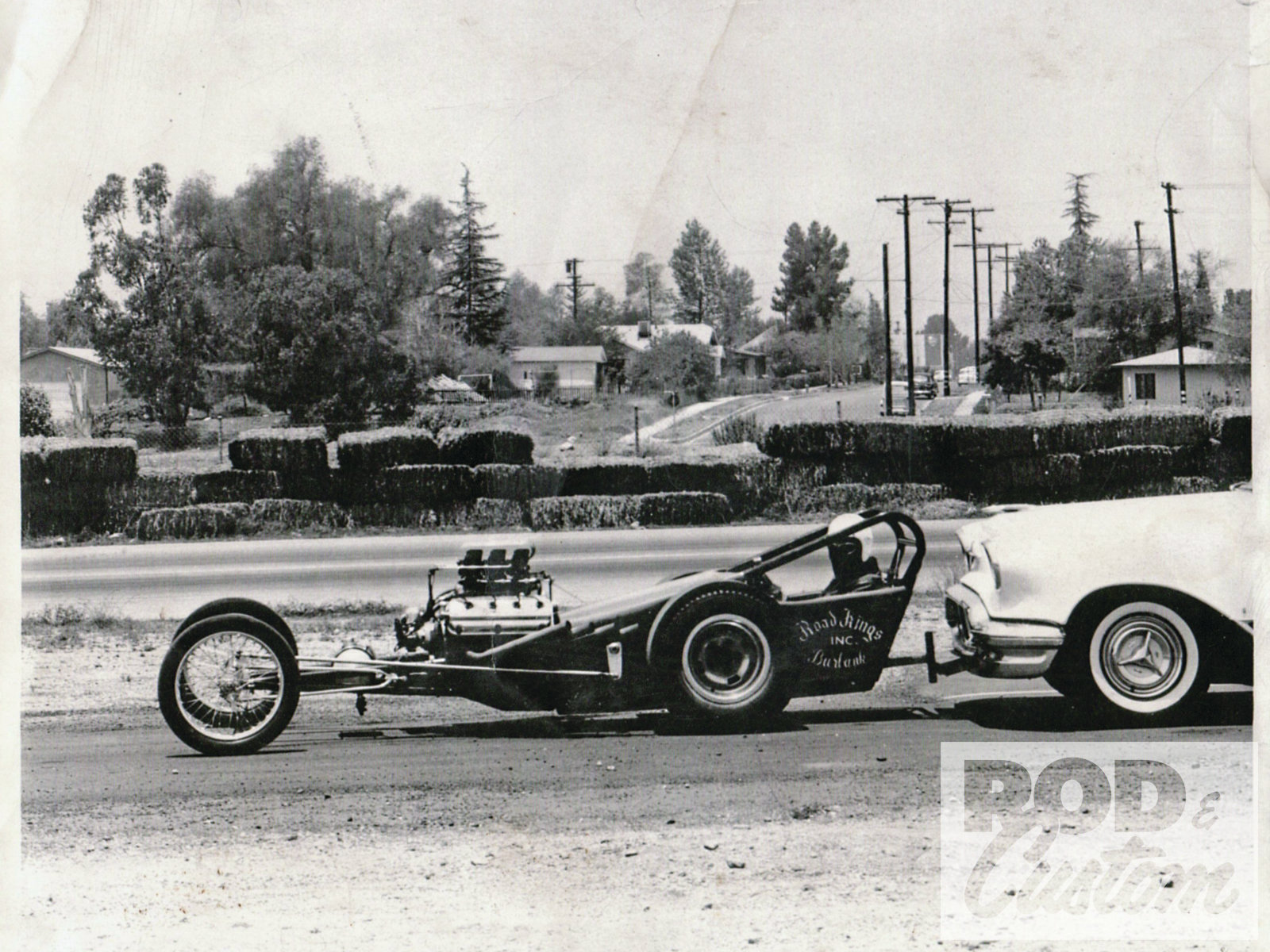 "Pictured is the Road Kings club dragster at San Fernando with Rod Peppmuller in his Olds pushing Don on the road after he come out of the pits. ""Rod Peppmuller was the chassis builder of the Road Kings,"" Don says. ""He built the chassis. We took it out to San Fernando, and Peppmuller and I drove it. And man, once I drove that dragster I was hooked."" According to Muravez, the dragstrip is where garage sales are held today."