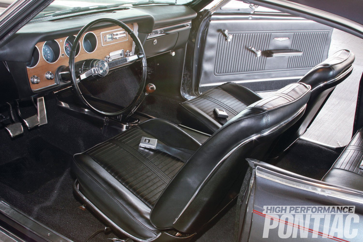 The black interior was restored using a host of reproduction components sourced from Ames Performance. Just the seat frames and kick panels are original. The only convenience options this particular GTO was equipped with are Custom seatbelts, front console, and pushbutton radio.