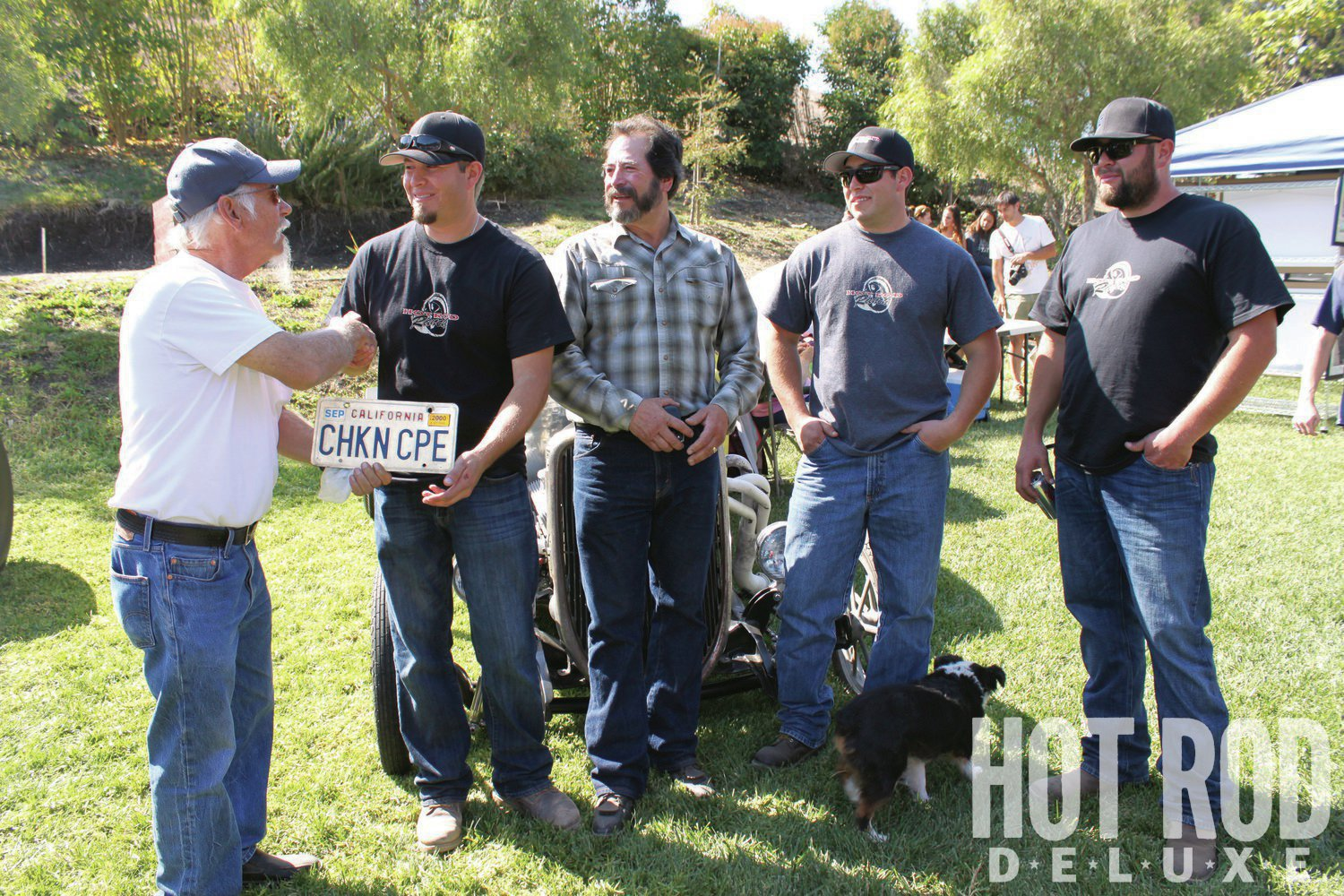 """Ed Potthoff (left) came out to the Hot Rod Ranch's Gasser Reunion and presented the license plate he ran on the car to Gil, passing the torch and closing his chapter of the car's ownership. """"I wish I had it back,"""" Ed said more than once during the show. Next to Gil are (from left) his father, Gil Sr., and brothers Randy and Jamie."""
