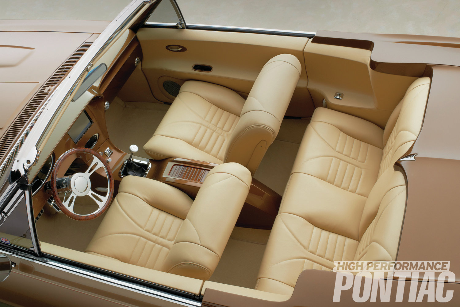 In Barista Pearl and Crème Brulee, the two-tone interior perfectly complements the Mocha Nut exterior. The seat frames remain the GTO's originals, but they've been reshaped using new foam and covered with new leather. Door and rear-seat panels were crafted by Run Rite Classics and wrapped in matching leather. The center console is a custom unit created by Run Rite Classics.