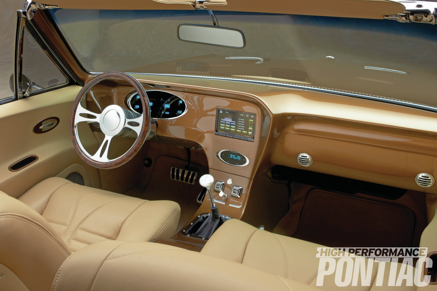 The custom dash panel is a fiberglass unit created by Run Rite Classics. Dakota Digital supplied instrumentation and a Vintage Air unit provides heating and cooling. A Fastlane steering wheel from Billet Specialties is mounted onto the company's tilting column. The in-dash Anbotek stereo uses a 7-inch screen that also functions as a GPS unit and displays the view taken by the back-up camera. The center console houses the power-window switches and pushbutton ignition.