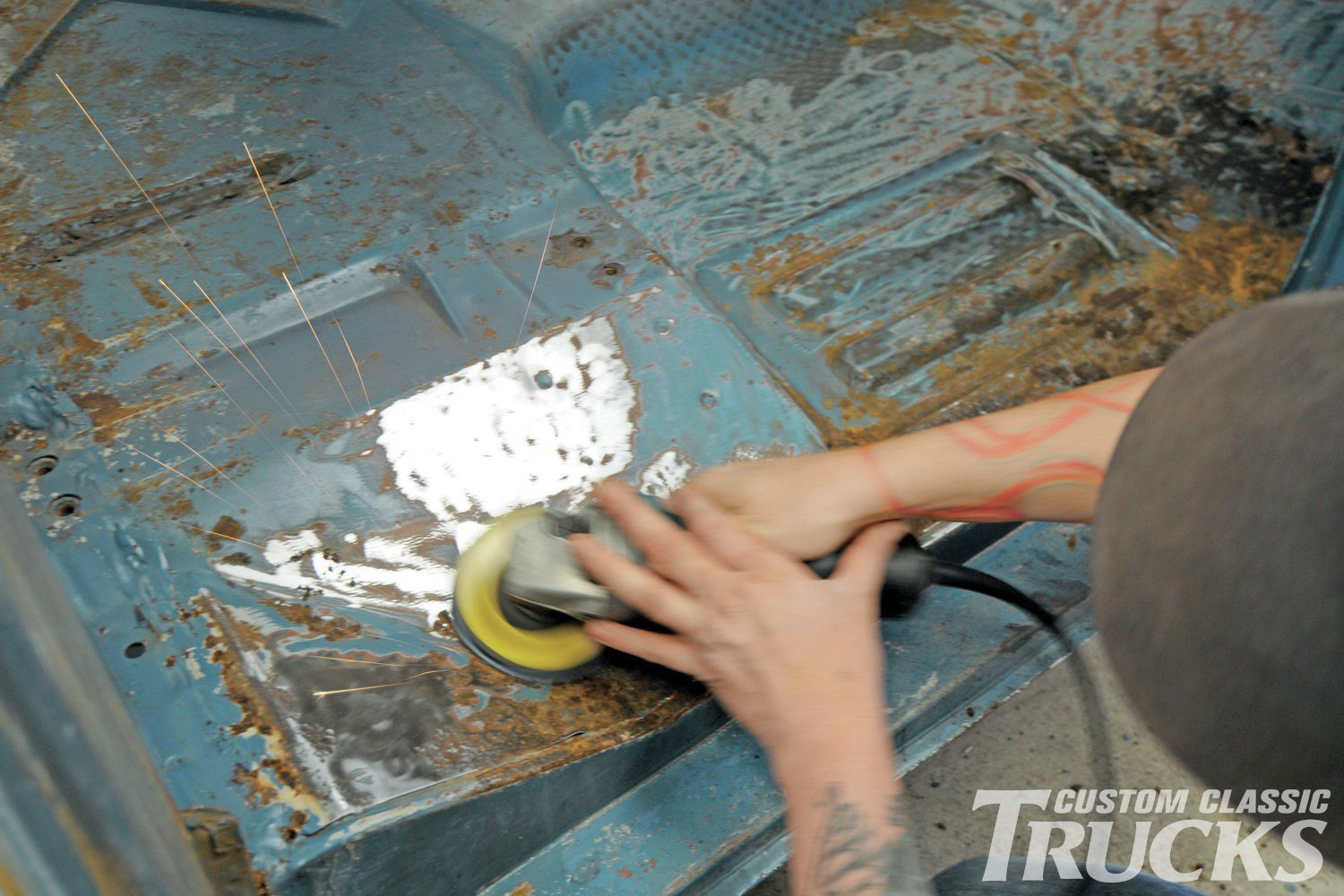 3. Rusty uses an 80-grit flap disc to grind off the paint and rust that was hiding under the old interior.
