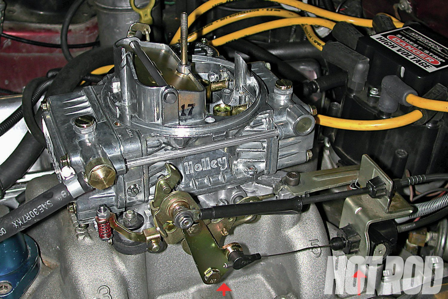To attach a GM TV cable to most modern 4150/4160 Holley carbs (except some race-only models with cut-down throttle linkage), use Holley cable mounting bracket PN 20-95 (A) plus throttle-arm extension PN 20-121 (B). Both must be used to obtain correct cable geometry. Equivalent TCI parts include PN 376705 (bracket) and PN 376715 (throttle-linkage adapter).