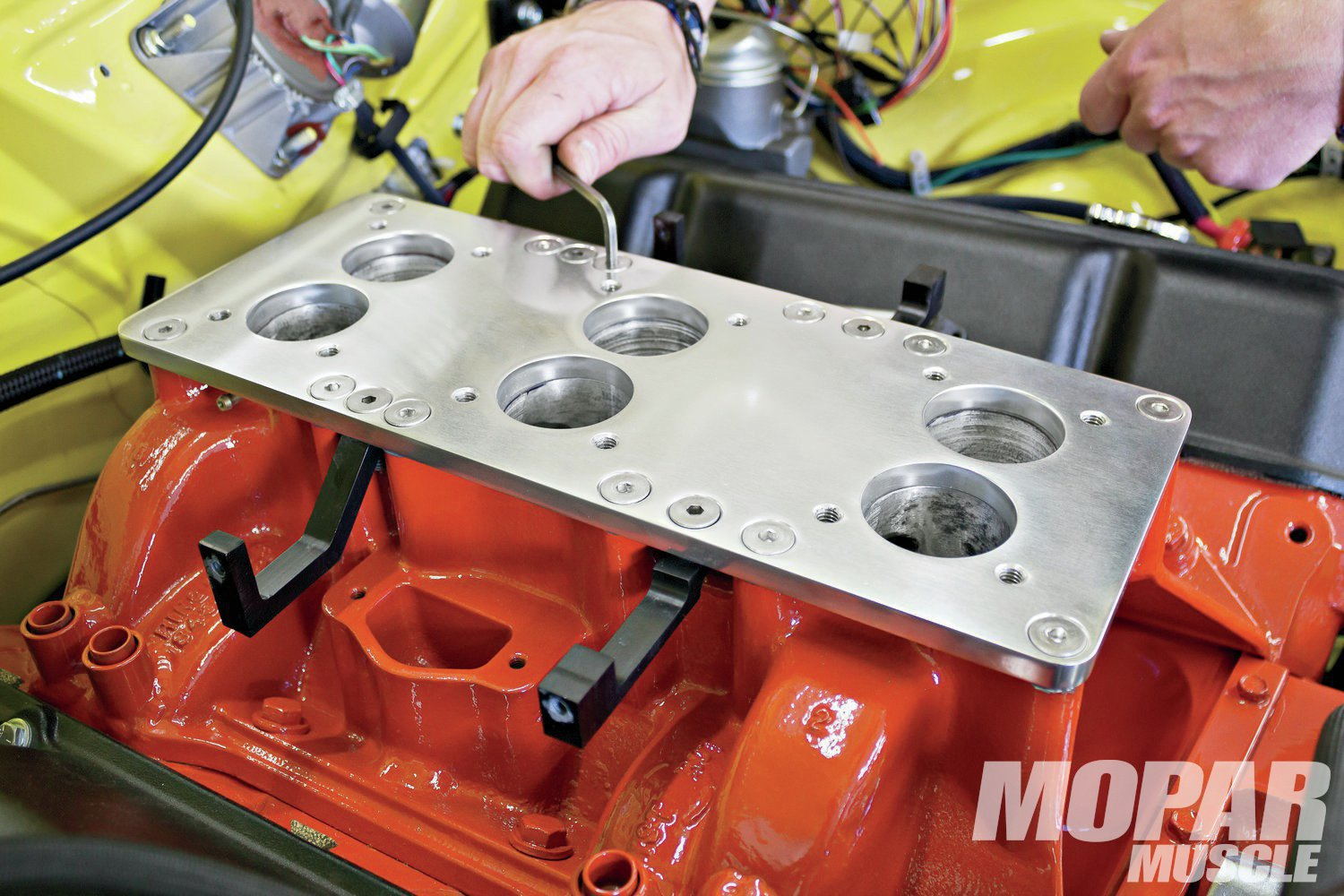 02 Because the throttle bodies' bolt pattern is smaller than the original Holley carbs, a spacer (also polished billet aluminum) is needed to provide the proper mounting pattern. It also provides a place to attach the fuel rail mounts.