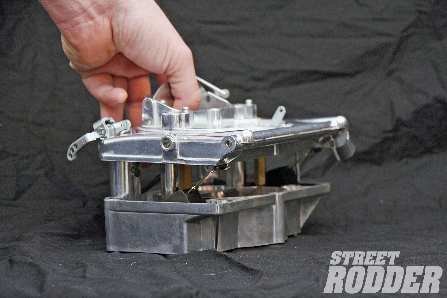 "Remove the bolts, and all the ""guts"" lift off with the top of the carb's body—float bowls, jets, metering rods, accelerator pump, and so on, are all accessible. This makes jet and needle changes incredibly easy, and clean, because the components are right there, while the bowls don't need to be drained. Initially, Rob and Lamar Walden found it was a pain because the four screws in the bottom necessitated removing the carb every time for changes while tuning on the dyno—until they discovered the four screws in the bottom can be left out during tuning, as the two through the top will hold the carb together, allowing them to keep the carb bolted to the intake, and just remove the top."