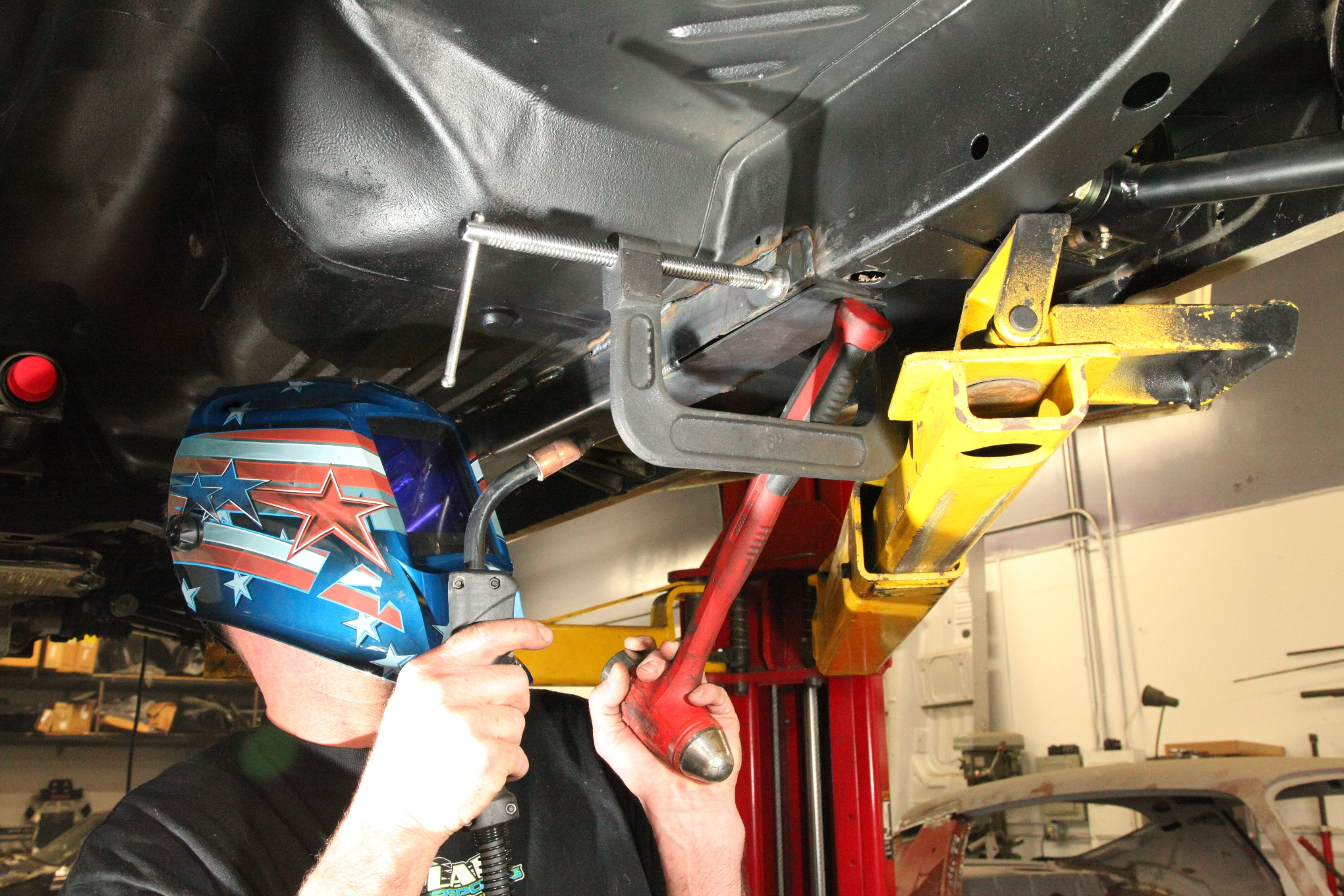 Before welding the rear framerails, the sides of the subframe connector need to be drawn against the factory rails using a large c-clamp. The handle of the hammer is being used here to pinch the top piece to the rail as it's being tack welded.