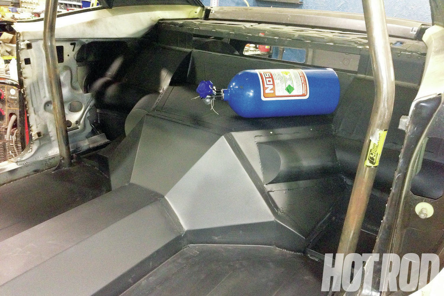Inside, the floor of the car shows the round ducts that channel air from the quarter-panel to the coolers mounted above the transmission. A Competition Engineering rollbar was added as the floorboards were being wrapped up.