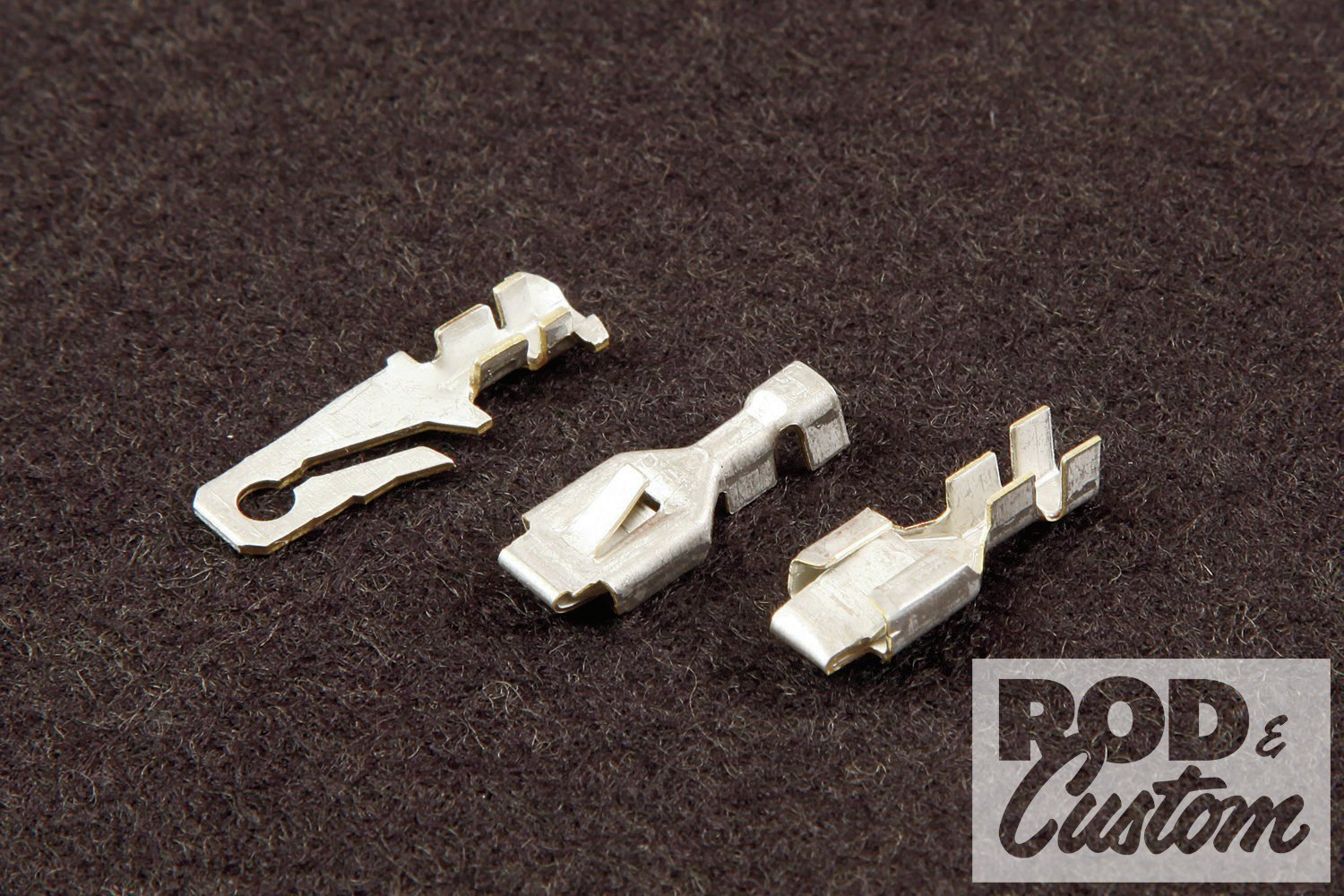 2. The female Packard 56 connector resembles a plain push-on terminal. The foreground terminal shows how it folds in on itself to maintain contact with the male terminal. The middle terminal shows the tang that locks it into its connector. The background terminal is the male.
