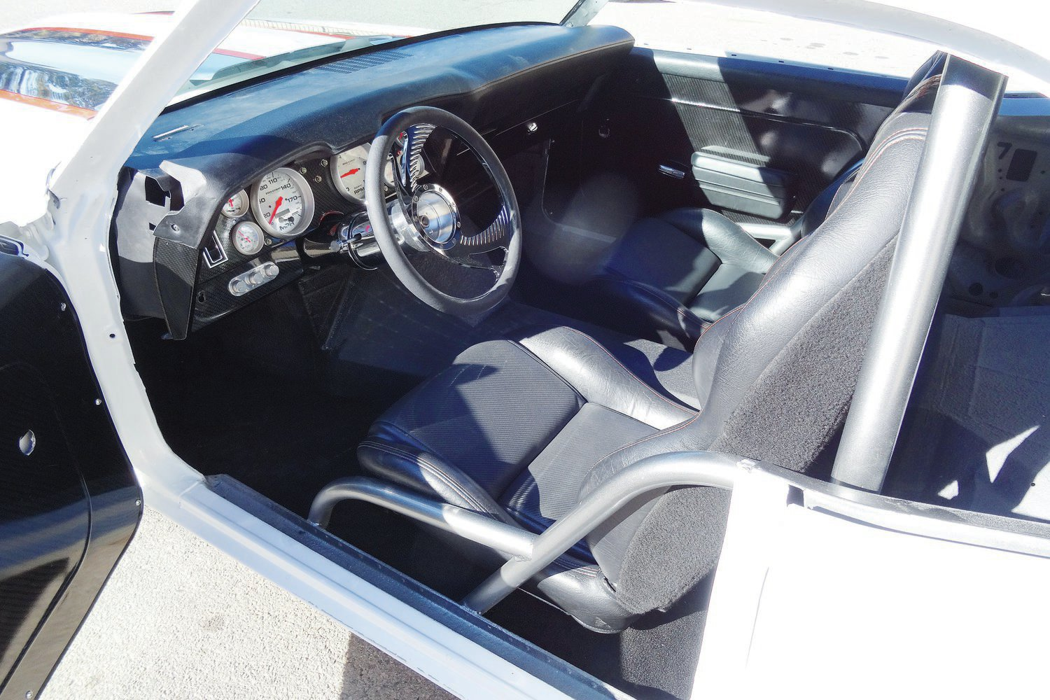 The interior view shows that the rear engine does intrude a bit into the passenger compartment. American V8 Classics and Customs lengthened the ididit steering column and dash and moved the seats rearward to compensate.