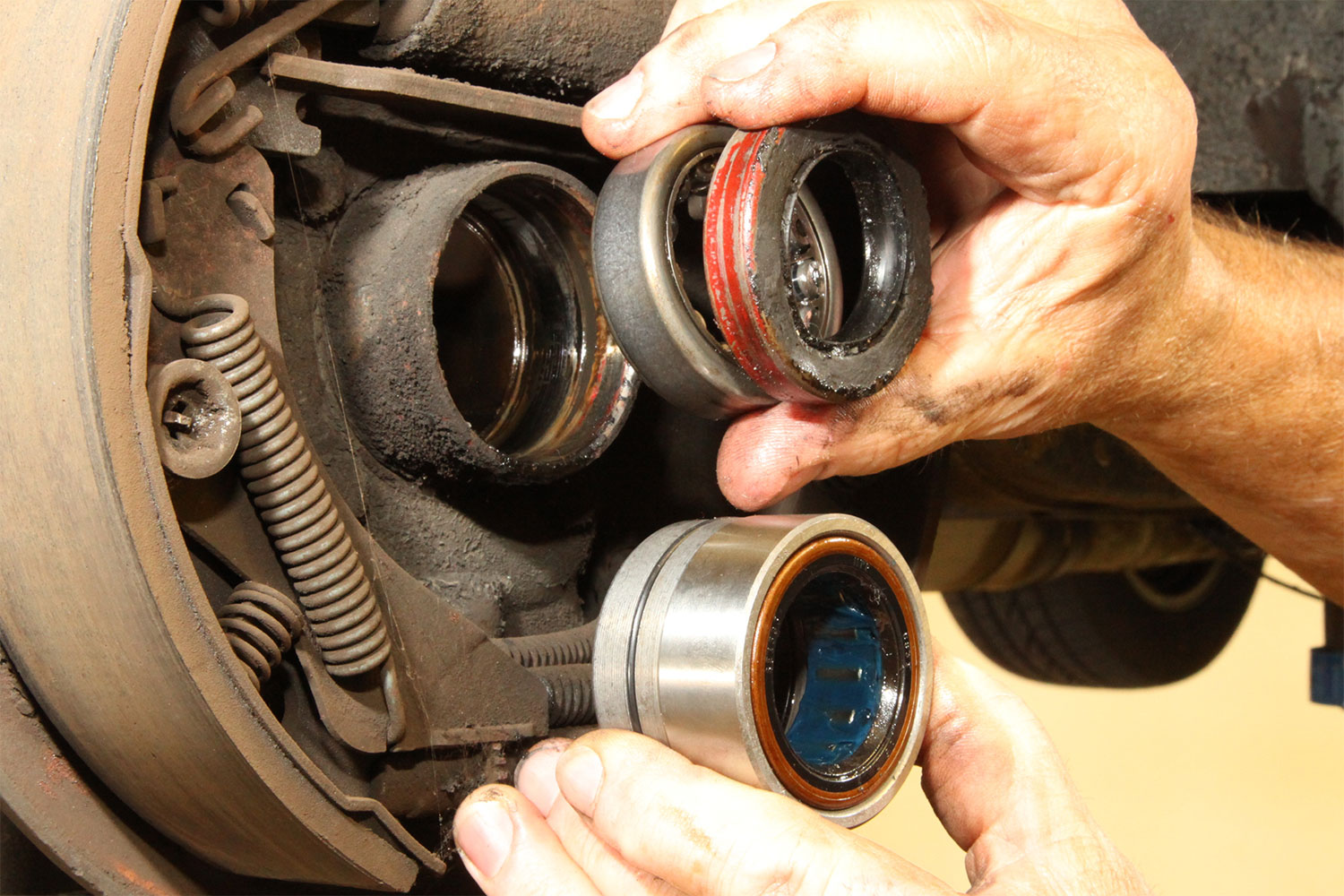 On top are the separate pieces for the OE bearing and seal, at the bottom is the new Timken unit (part No. TRP1563TAV, $27.97 Summit price) which is both the bearing and the seal. Note the locating ring inside the axle tube. This is the surface the bearing must seat against when installing the new unit.