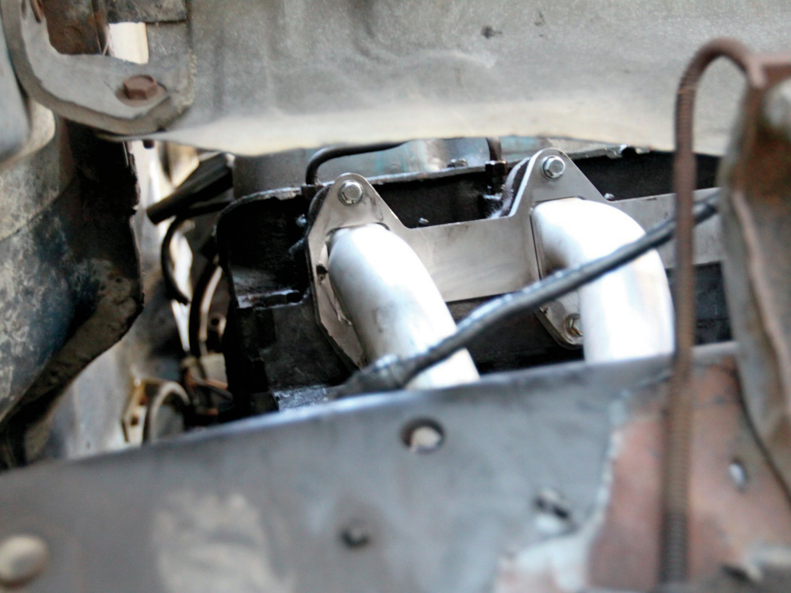 21. Tightening the header bolts on the passenger side was accomplished partly by accessing bolts through the fenderwell and frame.