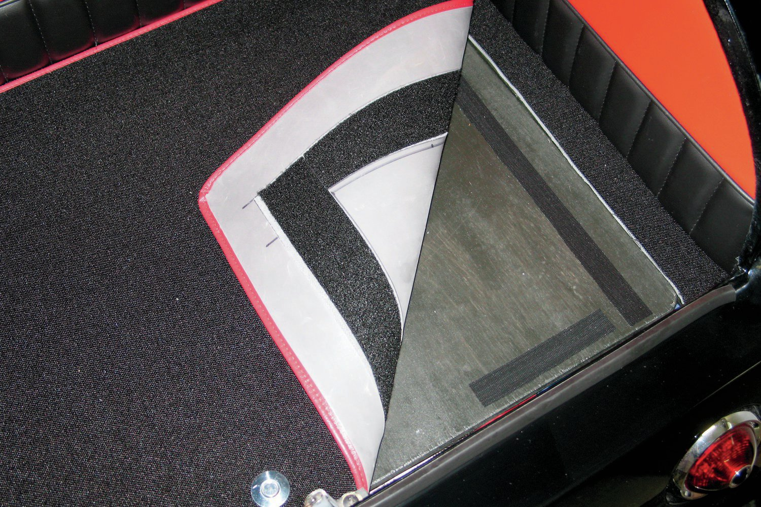 Velcro was attached to the false floor door and the carpet that would cover the door. This method allows you to move the carpet around and to remove it for cleaning or for easy replacement should something go really wrong down the road. Note how the carpet on the door overlaps the false floor edge carpet.