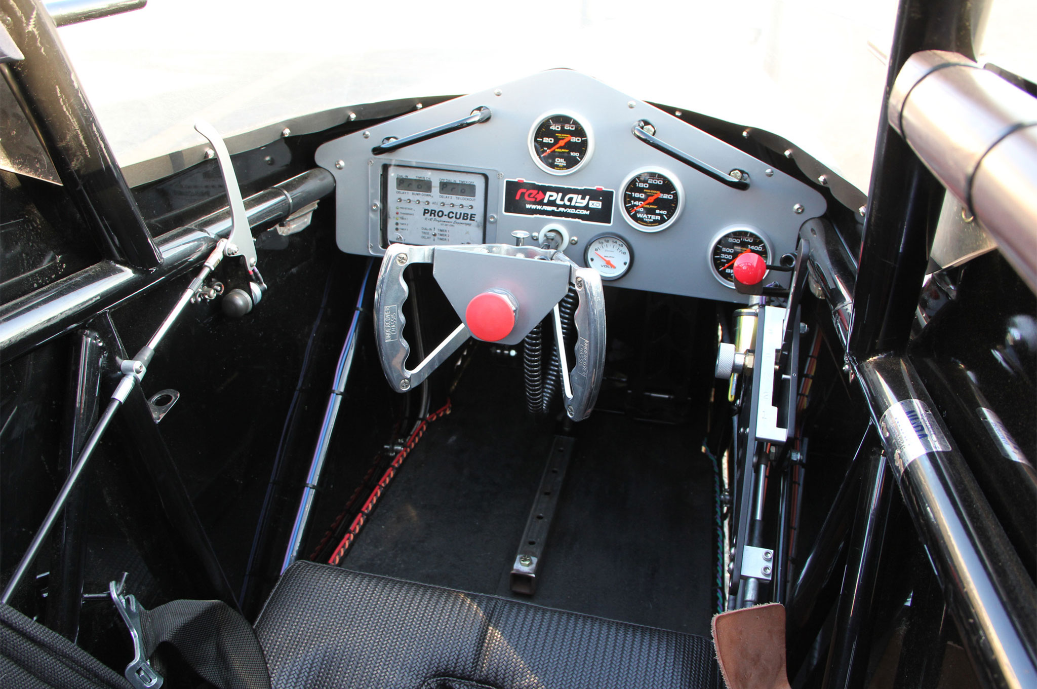 In the center of the wheel is the kill switch. To the right is the unused trans brake button and shifter. The small black button on the left starts the car.