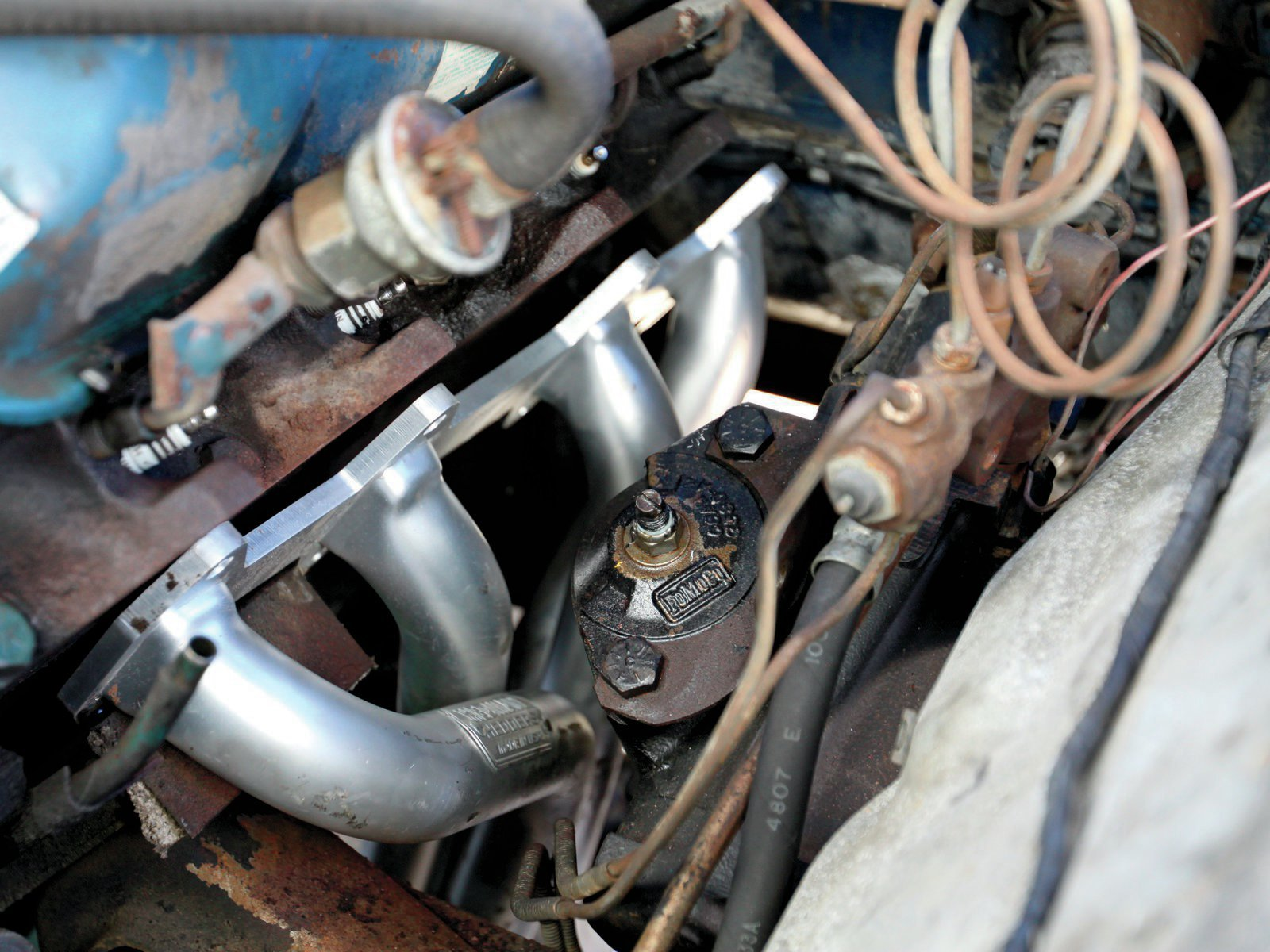16. The driver side header installs from the bottom. For stick-shift models the clutch linkage will have to be removed for clearance. Note the smog pump rail remains in place.