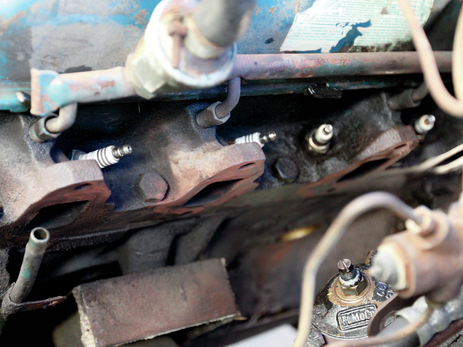 14. To avoid exhaust leaks a good clean surface is needed: I sanded and scraped the exhaust port face clean before mounting the header. Note the factory motor mount heat shield will have to be bent down to allow clearance for the headers on each side.