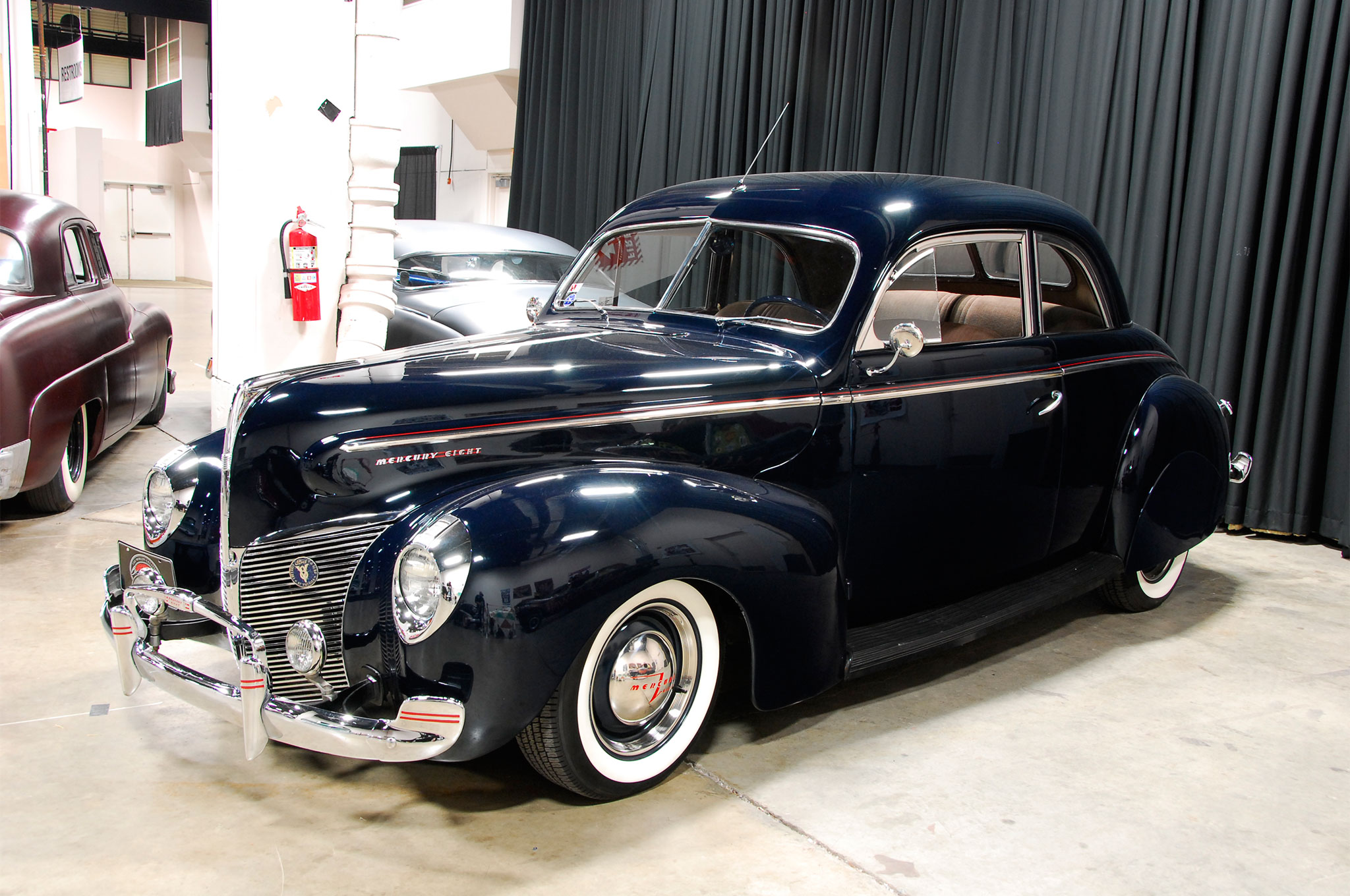 Sometimes all you need to do is set the stance and add just the right amount of detail to your ride to make the scene. This '40 Merc coupe looked right with its deep blue body accented by red pinstriping, perfect plating, and rear skirts.