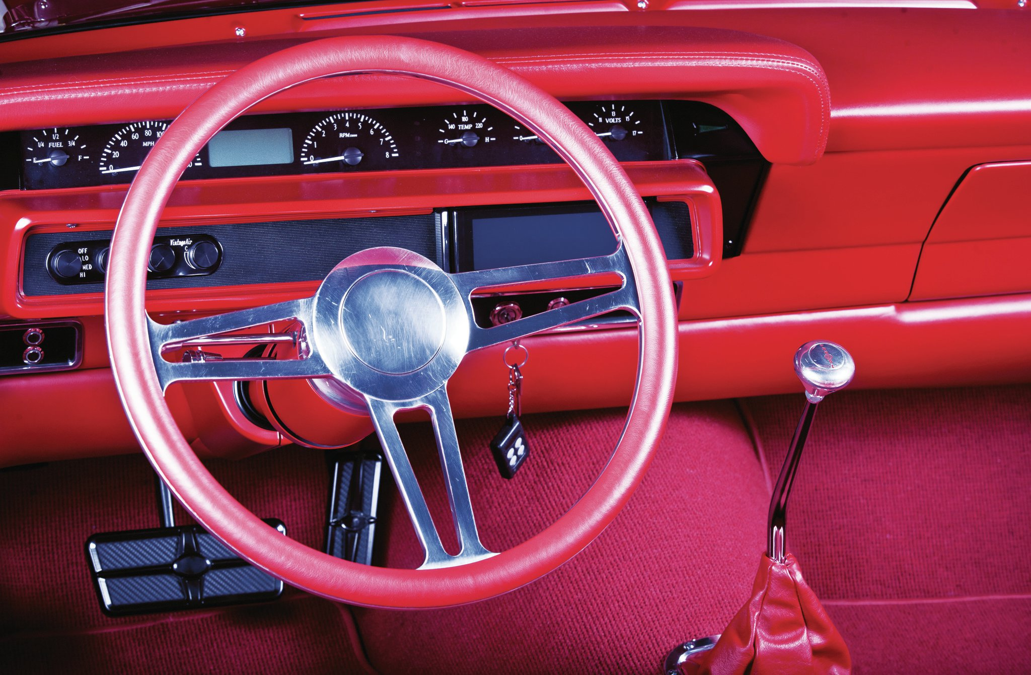 "Dave Kindig describes his custom, leather-wrapped billet steering wheels as an ""Oreo"" because there's billet in the middle and leather on each side, so the driver doesn't have to grip hot aluminum. Dave had Dakota Digital whip up a custom set of VHX gauges that fit within the confines of the stock Galaxie instrument panel. Below the speedometer are the controls for the Vintage Air A/C, and to the right is the JVC head unit that controls Kicker 6.5-inch component speakers and 12-inch subwoofers."
