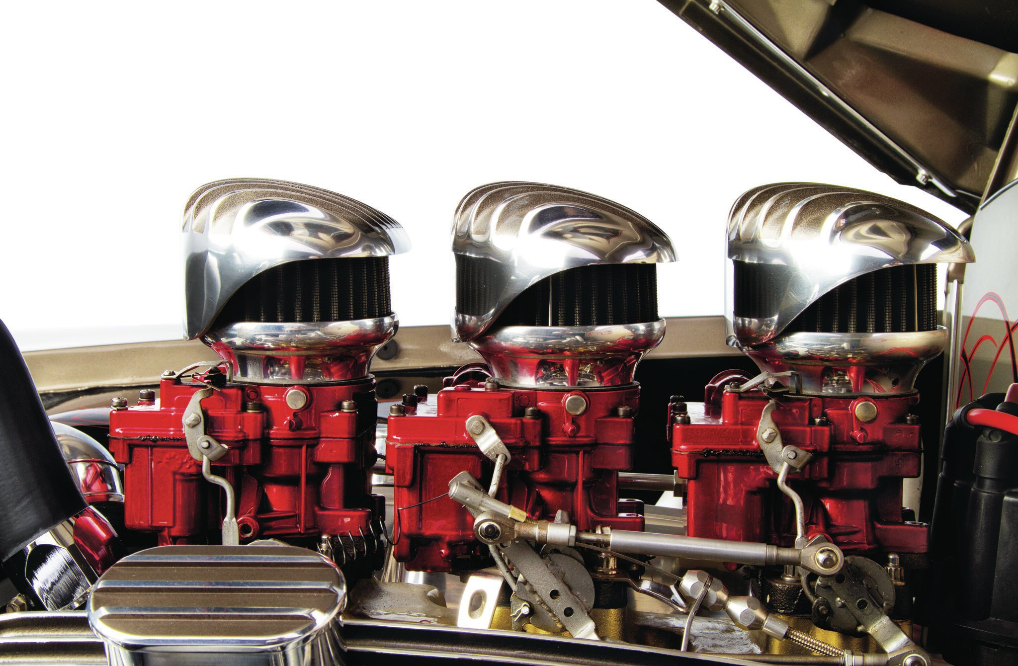 The 2-bbl Rochesters are powdercoated candy red to match the paint accents around the Cad and are complemented with retro-finned carb tops to match the finned valve covers.