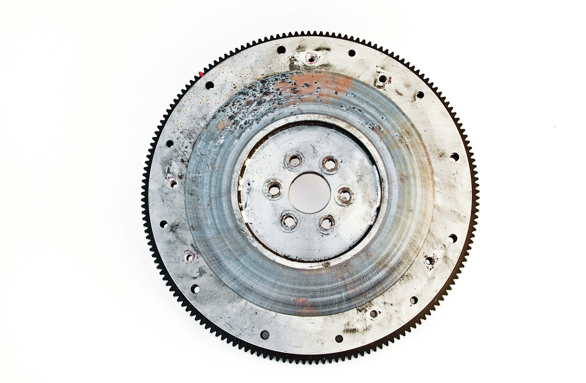 Bob's old Long-style flywheel, three-finger pressure plate, pilot bushing, and mechanical throwout bearing showed signs of improper installation, damage, and overall distress. The beefy 2,500-pound pressure plate lacks the antirotation locating dowels like those found on today's race-style Long clutches. It may have developed too much pressure for the stock Ford mechanical clutch linkage. Note the broken clip (arrow) on the throwout bearing.