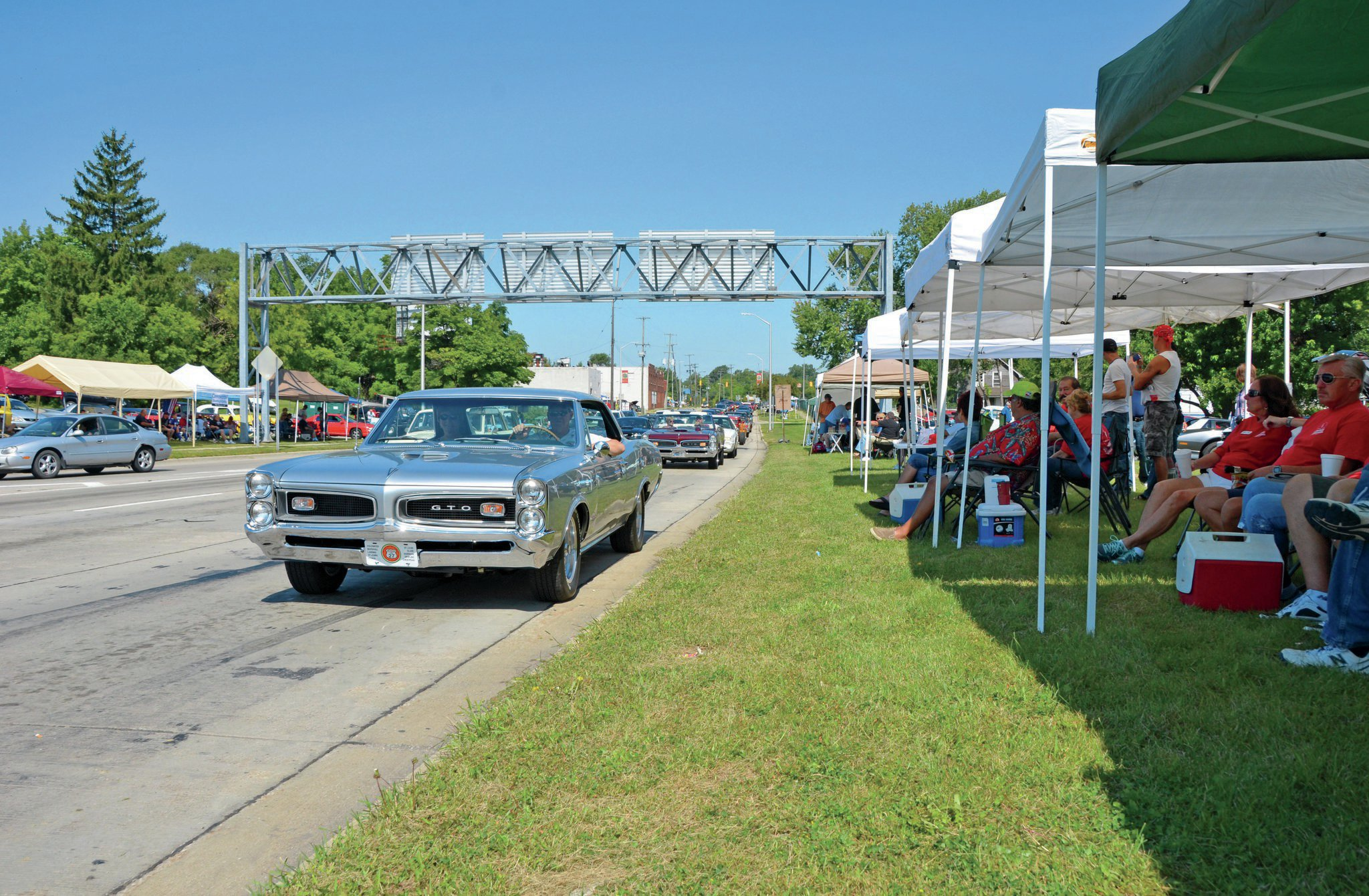 A '66 hardtop and a '67 convertible GTO cruise past appreciative spectators on their home turf, the Woodward Avenue business loop in Pontiac, Michigan. This is what Woodwarding is all about.
