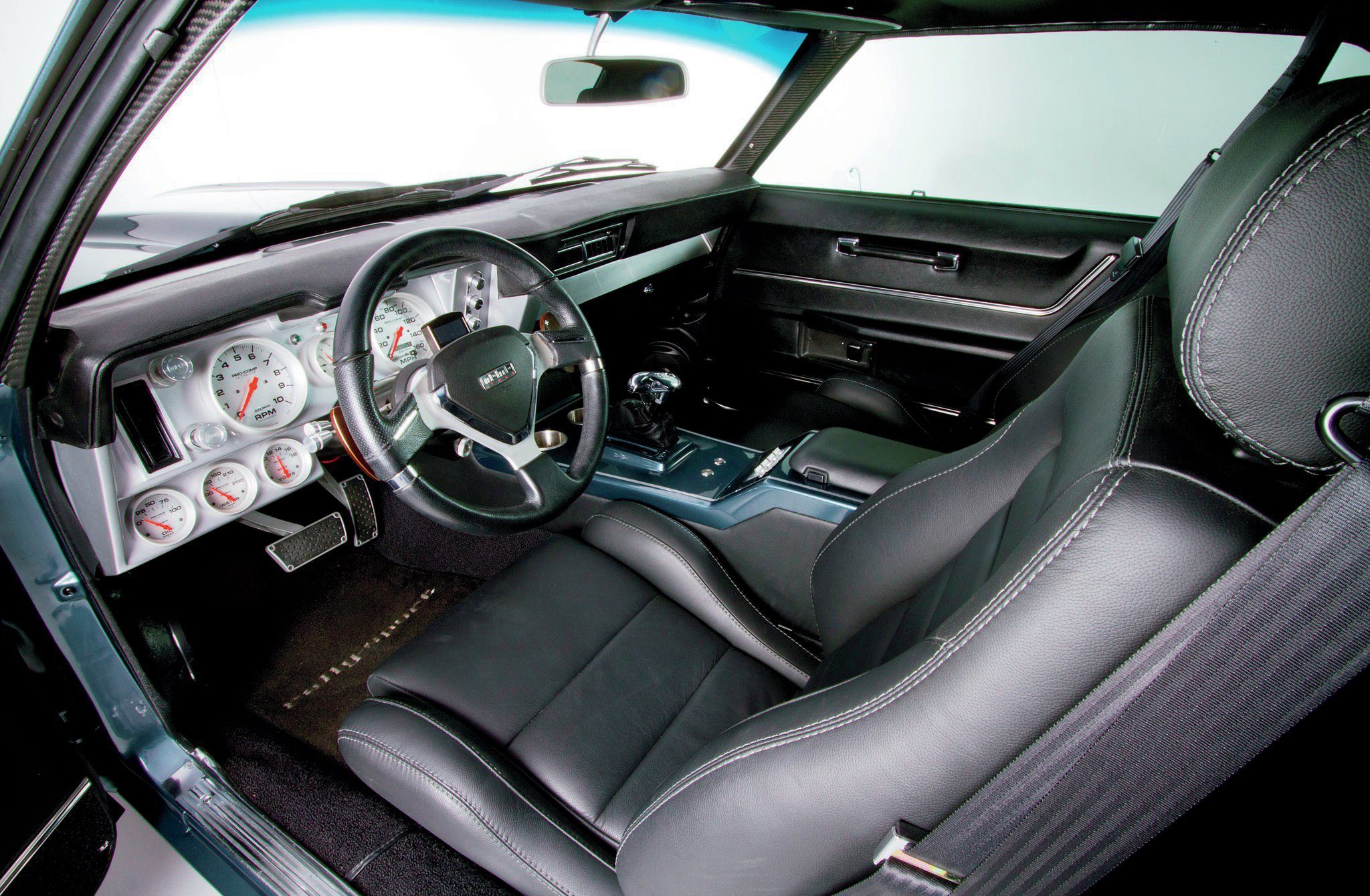 The interior has all the right modern upgrades, including Auto Meter gauges in a Detroit Speed & Engineering pod, Vintage Air A/C, ididit tilt steering column, MOMO steering wheel, and Corbeau GTS II seats leather wrapped with contrast stitching by Bill Dunn upholstery shop.