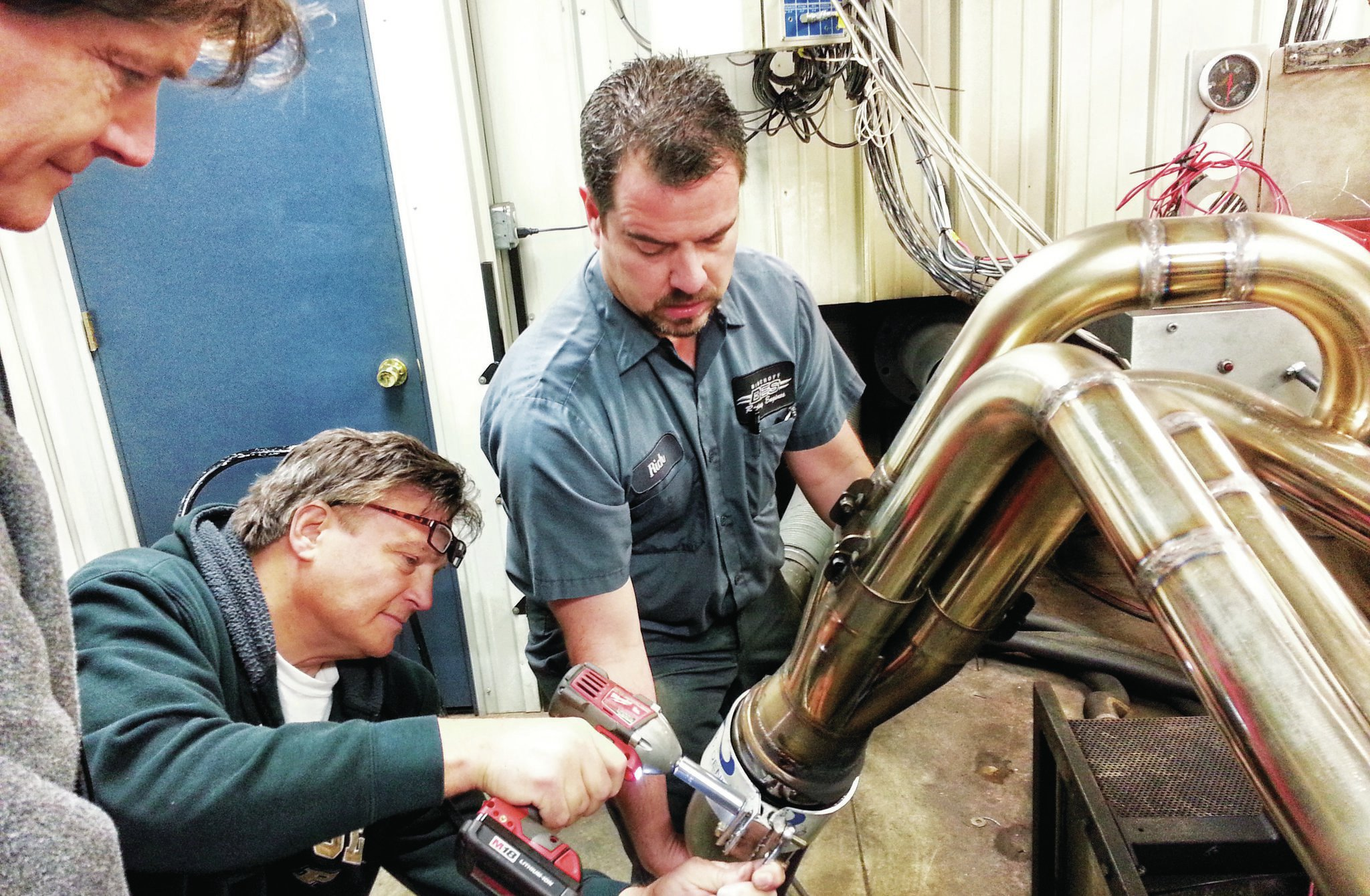 Lynn McCarty adjusts the header V-clamp while Rich, the dyno operator at BES holds the pipes up. Lynn's twin brother Stacy is observing their progress.
