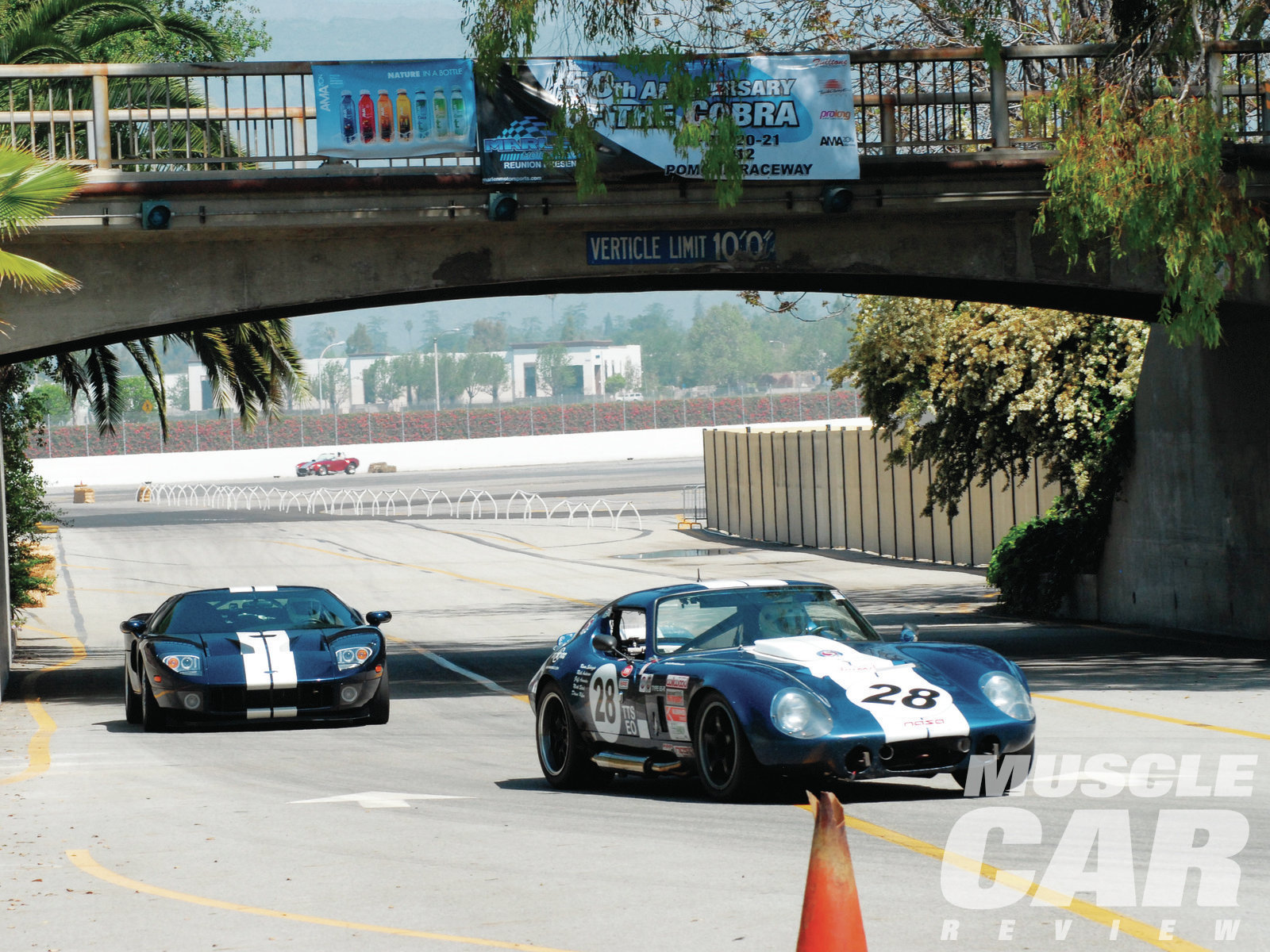 This Cobra Daytona coupe replica, driven by Karen Salvaggio, is being chased under the Los Angeles Fairplex crossover bridge by the Ford GT of Kevin Roberts.