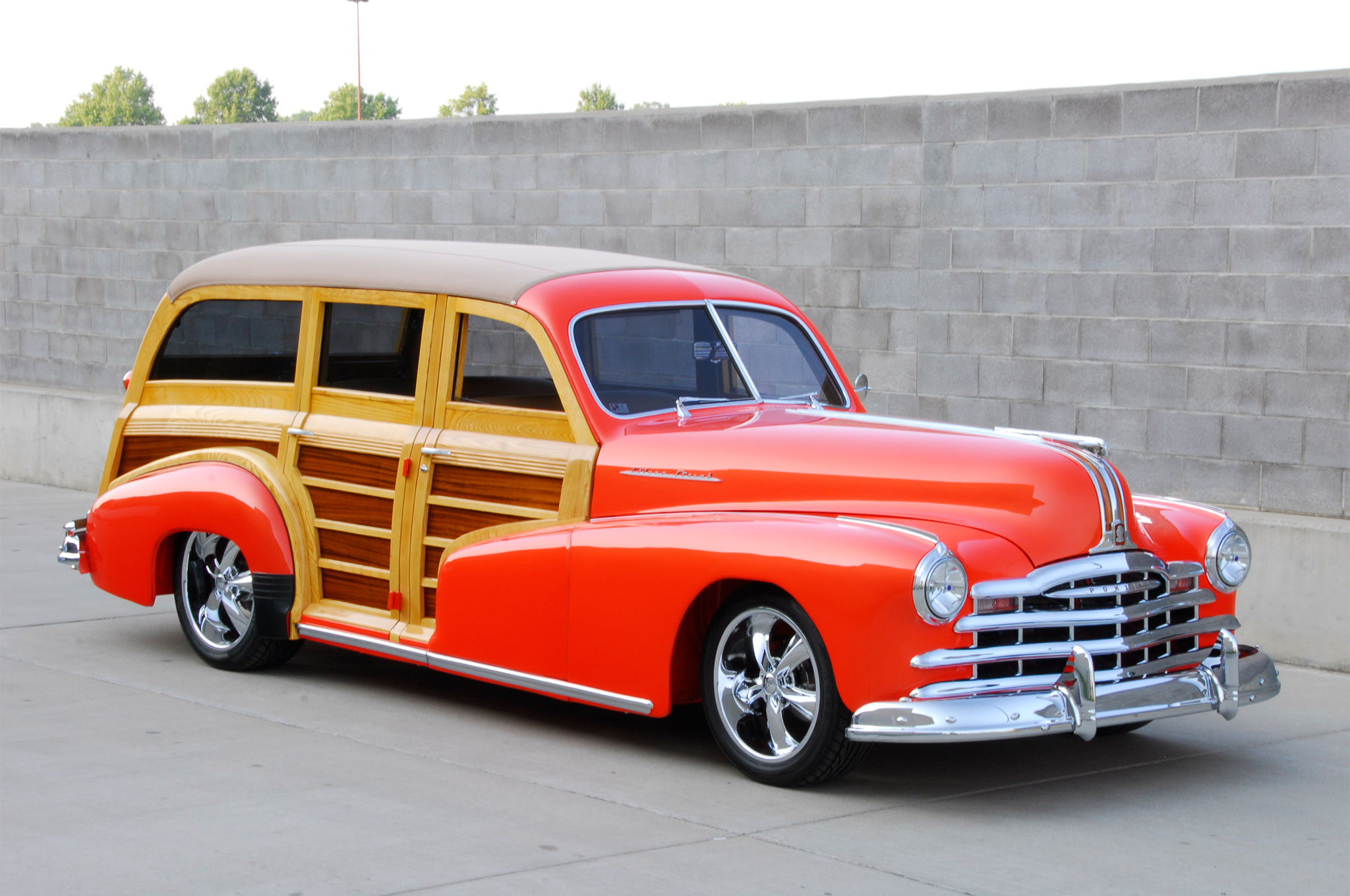 Big, bold, and coated in gallons of House of Kolor Mango Coral pearl, the wagon gives off a dramatic decadence rarely seen in smaller hot rods. Accented by miles of wood and chrome, it's easy to appreciate all of the intricate attention to detail.