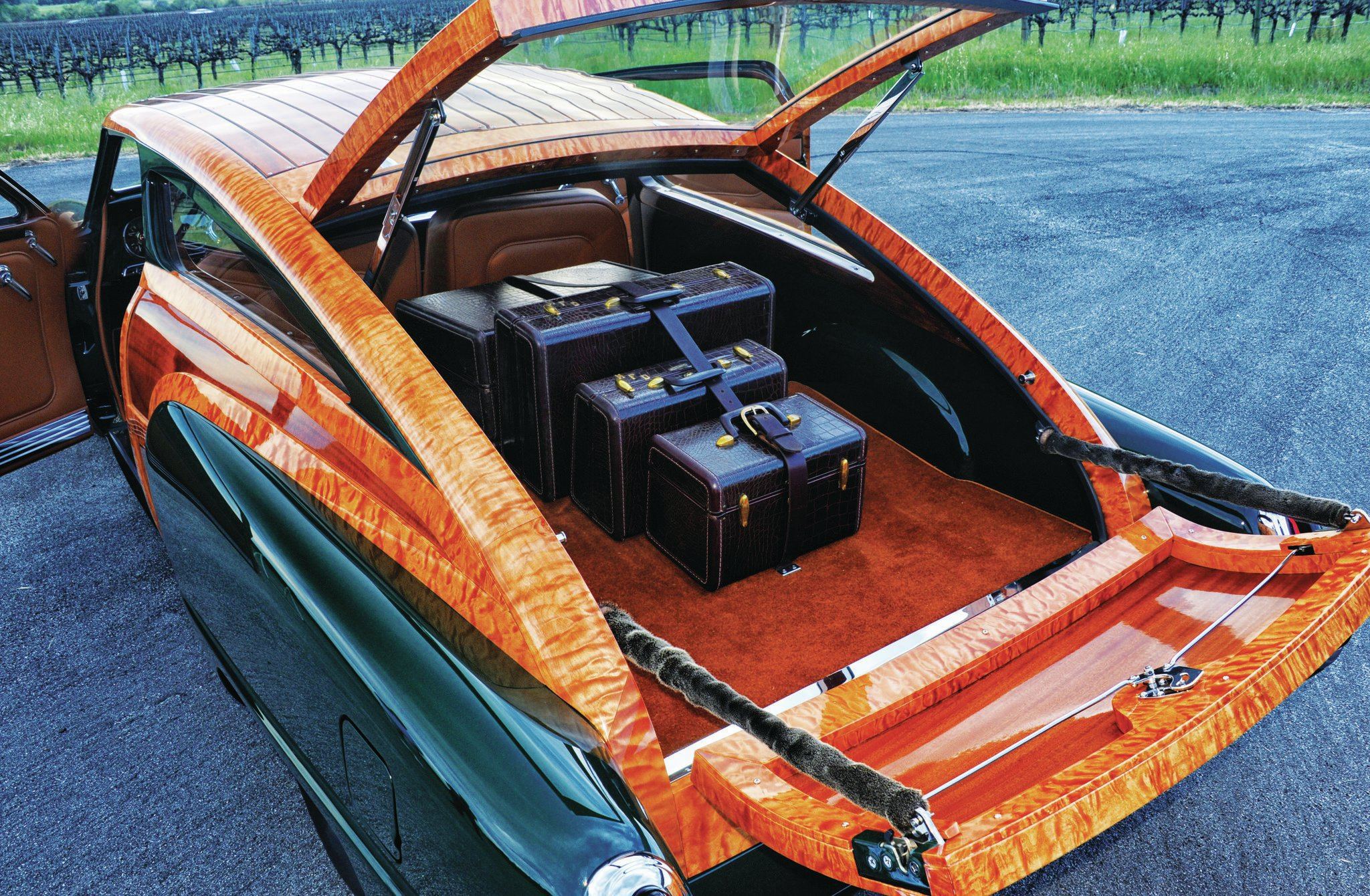 In Dennis' travels, he found this matching set of luggage in an antique store and thought they fit well with the woodie because the car is only a two-seater. Also note the functionality of the liftgate and tailgate, which, along with the painted sheetmetal insides, look factory stock but are not.
