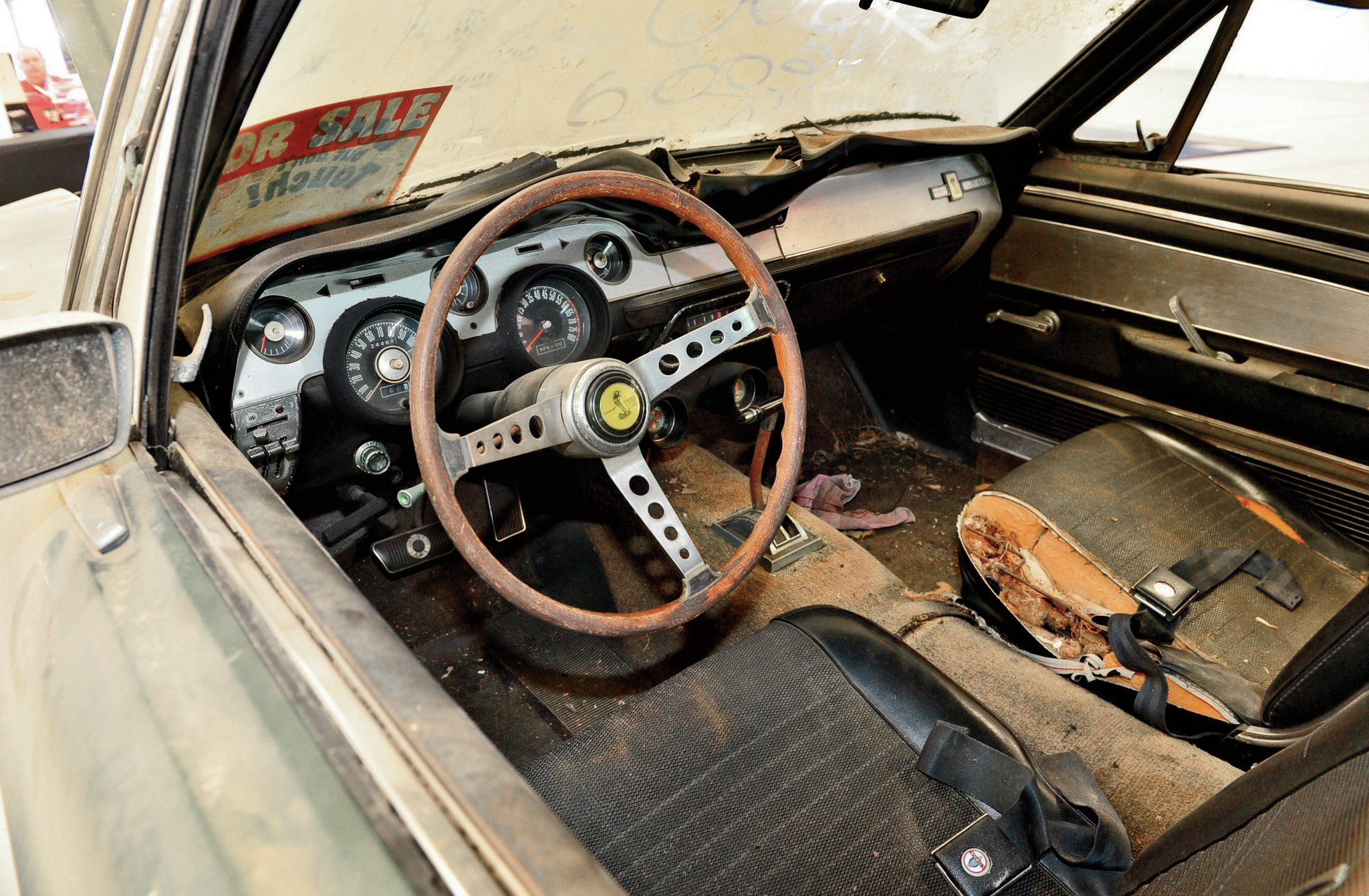 The interior is complete, including the wood-spoke Shelby steering wheel and Shelby gauge cluster. It could use new carpet and upholstery.
