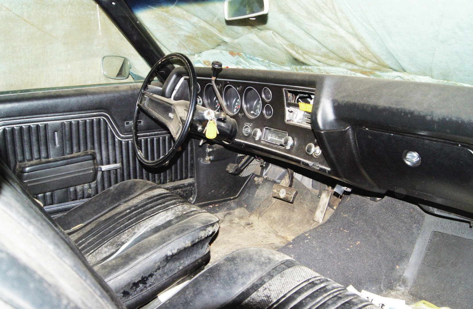 Except for a mold infestation, the interior is in decent shape. Note the factory radio is intact and the keys are still in the ignition.