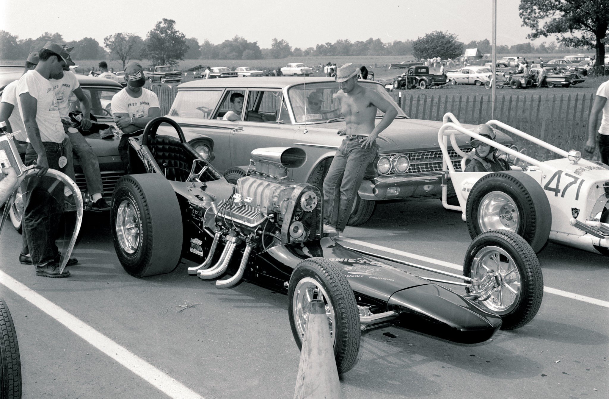 "This comparison of early '60s slingshots only begins to illustrate the impact of Kent Fuller's single-hoop chassis, Chuck Jones' design for the first ""'chute-pack"" tail section, and the only dragster body that Lujie Lesovsky ever built. Crew chief Rosy Hroscikoski put the pieces together and tuned one of the last competitive Pontiacs in both Top Gas and Top Fuel Eliminators, thereby earning the Shudder Bug's nickname of ""Eighth Wonder of the World."" Ernie Alvarado paid the freight with earnings from his Glendale, California, store, Ernie's Camera Shop. Tommy Ivo drove first, then Bill Alexander, who recalled how it never went straight unless he cranked the butterfly wheel hard to one side. Wild Bill ran out of luck at San Fernando, totaling the car that most influenced dragster design during the first slingshot era, and to this day in nostalgia racing. (Yeah, we're fudging the rules a bit by plucking a photo from late 1961 because the other driver looks so goshdarn envious, and we don't recall seeing this NHR"