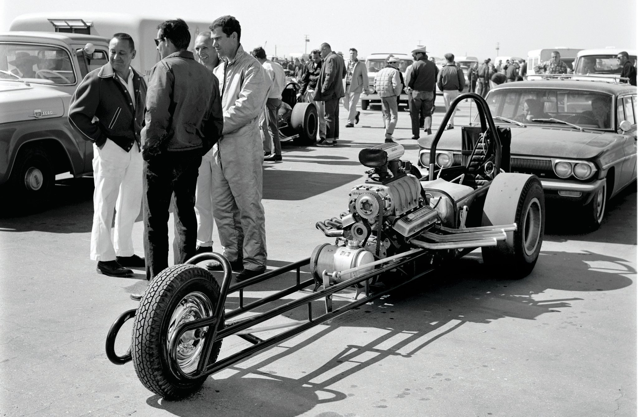 Tin-bender Kenny Ellis's unique slingshot is illustrative of this period's minimal mechanical restrictions and the unbridled innovation that resulted. Kenny built and successfully campaigned at least three different three-wheelers over a decade. He's shown (in firesuit) at the '63 March Meet. The guy in the white pants sure looks like Jim Tice, who grew his AHRA by running popular classes that rival Wally Parks would not.
