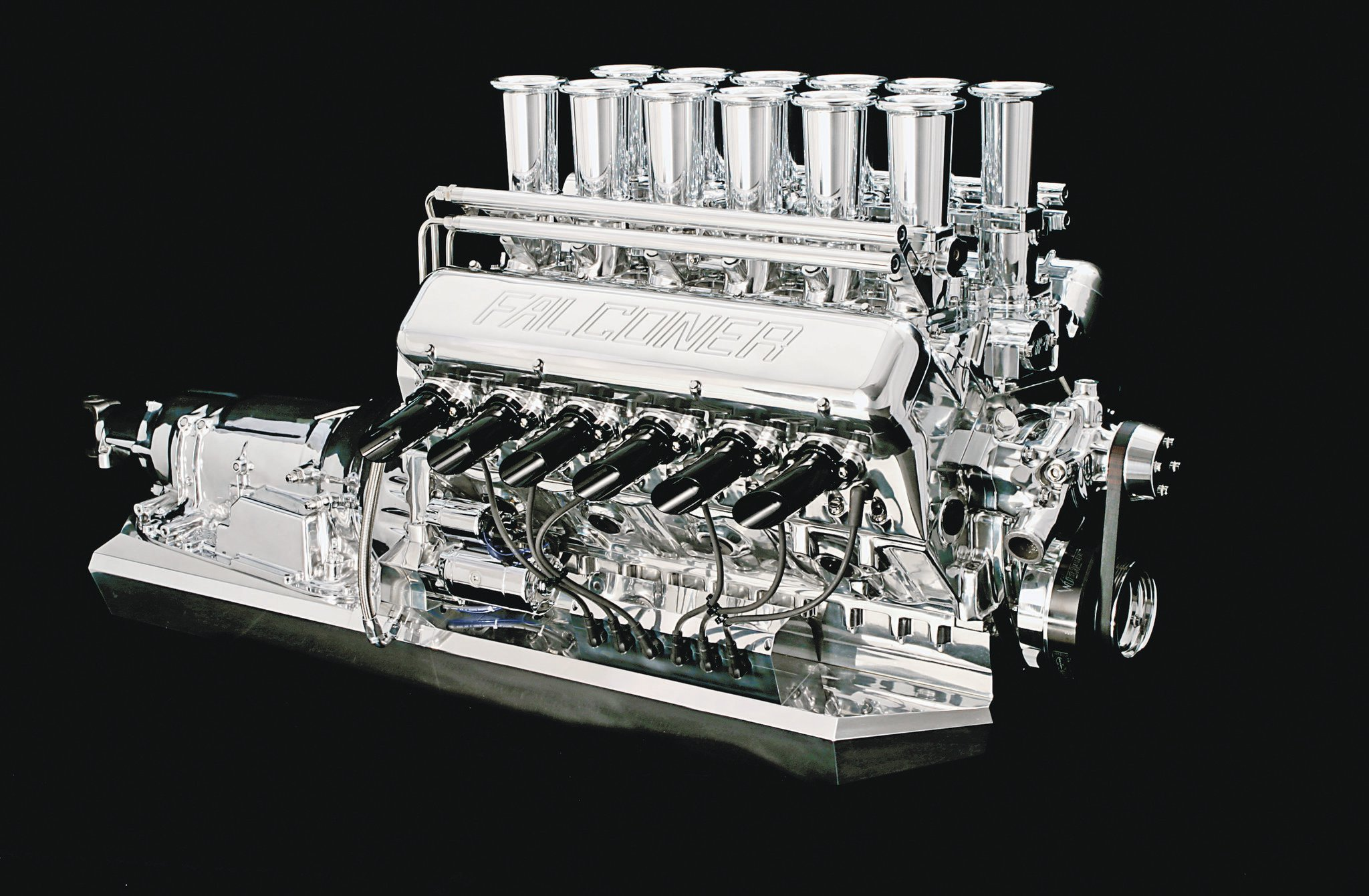 This Falconer V12 has nonstandard wet-sump oiling. Chip Foose currently has this engine at his shop. The engine oil pan, 4L80E trans pan, and the converter cover are three massive slabs of billet aluminum. Engine wiring routes through the oil pan's sides and is terminated with two Canon plugs. The extra fuel-rail really contains the injector wiring and connectors.