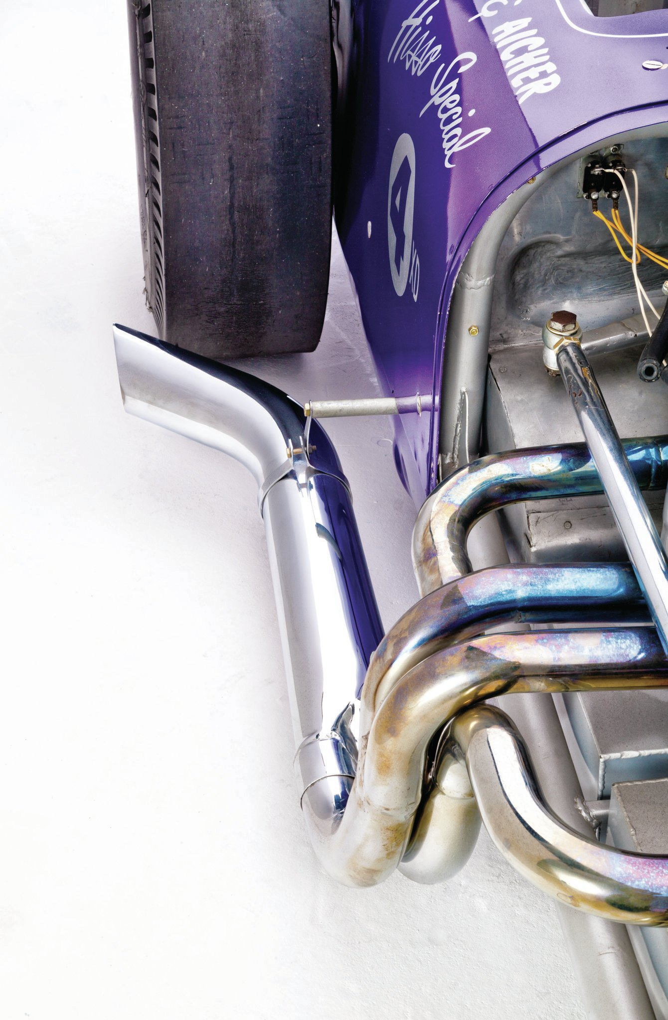 The fuel tank sits under the four-into-one header on the right side of the car.