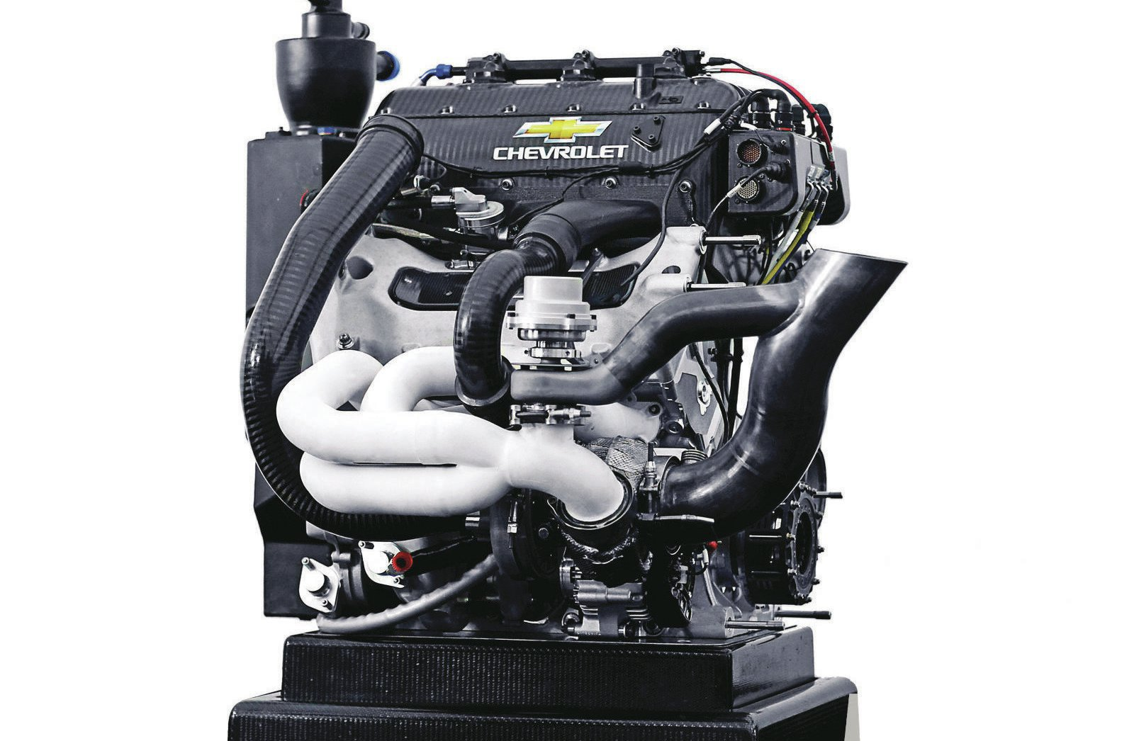 It's not often that an engine rewrites the rules of a race series, but when Chevrolet introduced its 2.2L twin-turbo V6 for the company's return to IndyCar, it took exactly one season for the rules committee to require a spec twin-turbo system to level the playing field for the far outclassed single-turbo Honda system. GM embedded top engineers with Ilmor Engineering (UK) to develop and manufacture race components and create the engine calibration. The cars are assembled and tested in the U.S. GM partnered with Hitachi to create the DI system, which we're told is based on production components.