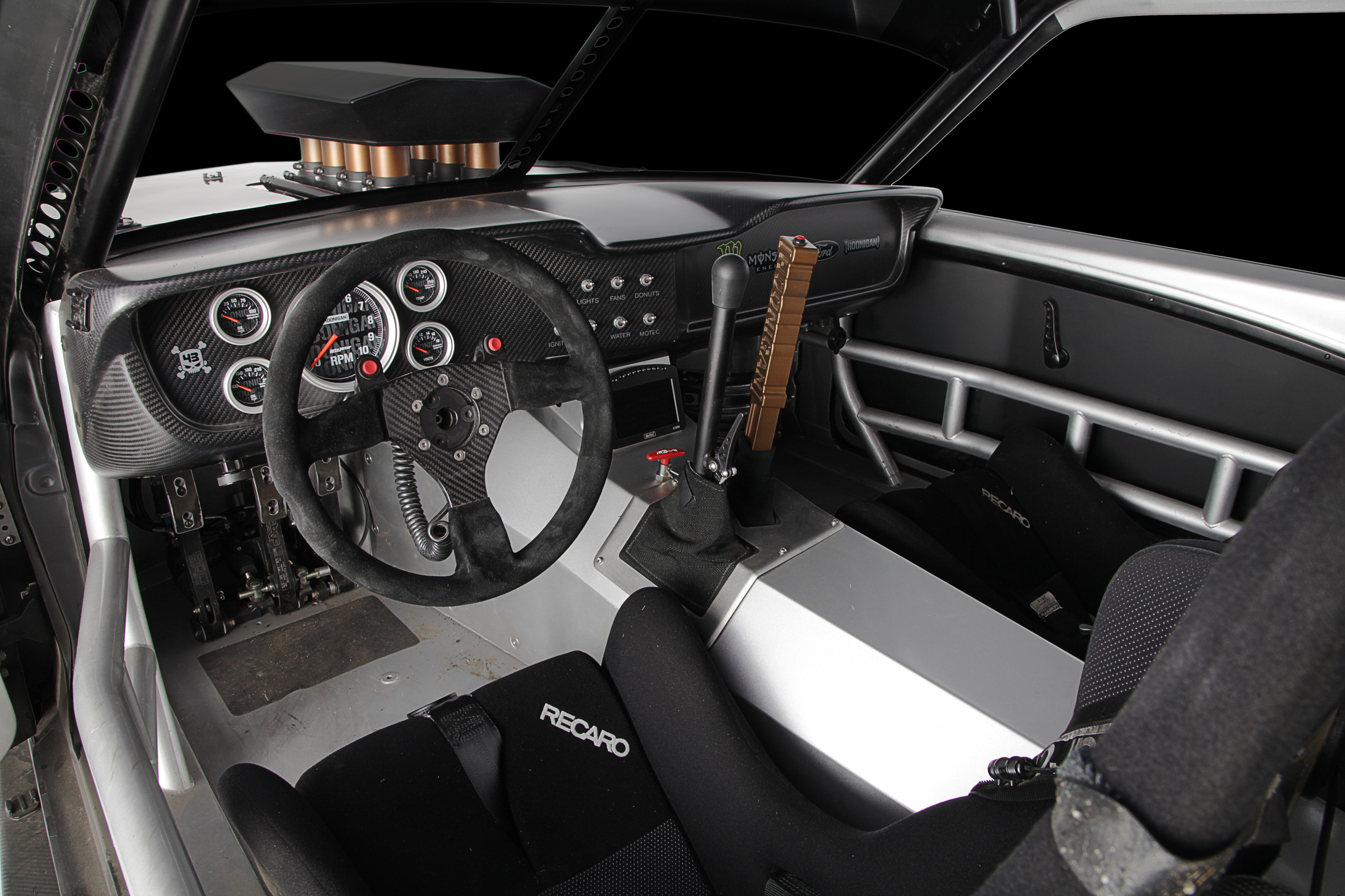 The interior is race car Spartan, with carbon-fiber dash and a bead-blasted aluminum trans tunnel. The handle nearest Block's driver seat is the shifter for the sequential six-speed Sadev transmission and the billet Hoonigan lever is for the rear brakes. Mounted at the forward end of the tunnel is a MoTec C125 data logger.