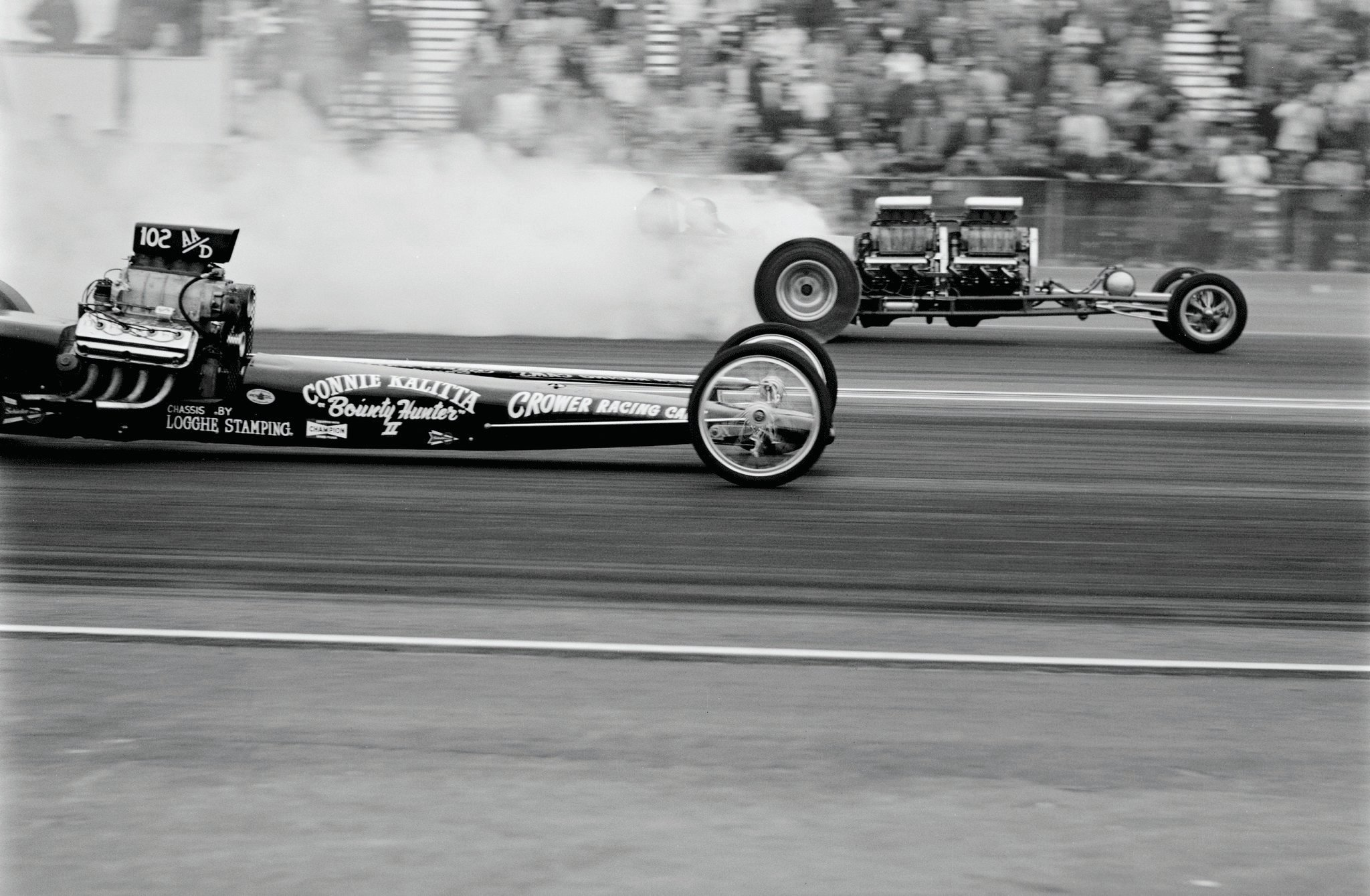 "Following frustrating outings at NHRA's '59 Nationals and '61 Winternationals, local kids John Peters and Nye Frank, both 23, notched two major upsets on the same February weekend at Pomona. Their homebuilt beast first beat touring pro Connie Kalitta in Saturday's AA/Dragster class trophy dash, and again in Sunday's ""Winter Top Eliminator"" final. (The unfilled grandstands and a HOT ROD photo of these cars in opposite lanes lead us to believe that this is the class race; not Sunday's grand finale, as previously reported.) A clean sweep of the third annual Winternationals further included both low e.t. (8.36) and a top speed on gas (185.18) that was faster than some fuelers' times. More memorable yet was the postrace masquerade that successfully concealed their driver's identity. The entry form—and subsequent press coverage—erroneously named Peters (second from right, inset) to prevent Bob Muravez's disapproving father, also his employer, from learning that Bobby was disobeying family orders to vacate the seat."