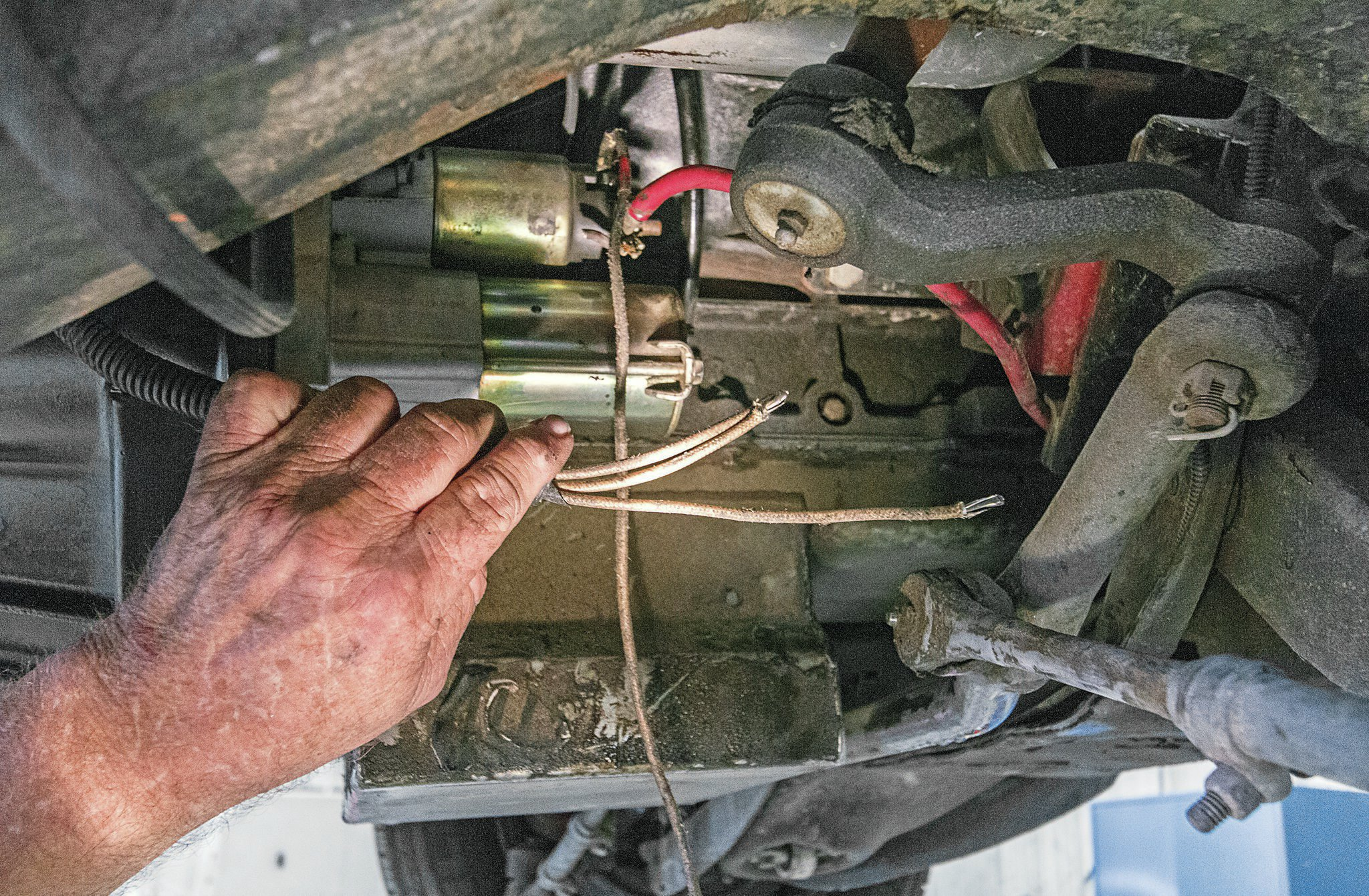 "While he was bending up the new fluid lines, Norm noticed the dangling engine starter wire harness. ""I couldn't just let that lie,"" remarked the meticulous mechanic. ""I cut 1 foot out of the wires, cleaned up the routing, and secured everything out of the way."""