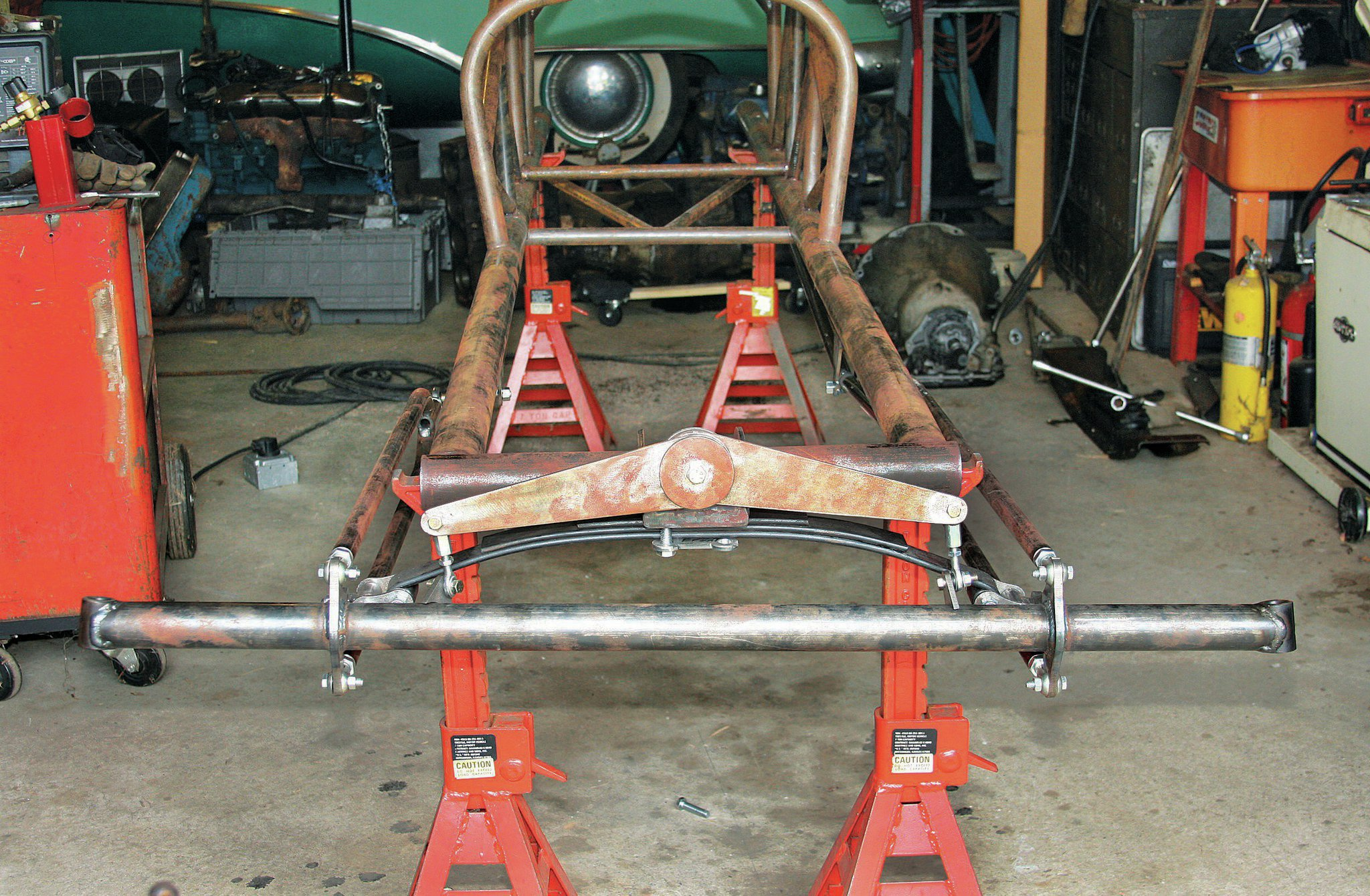 The front axle assembly, installed with the friction shocks (though the axle's shock mounts aren't welded on yet). The axle looks as wide in person as it does in this pic! But studying a couple other photos of the original, it looks right.