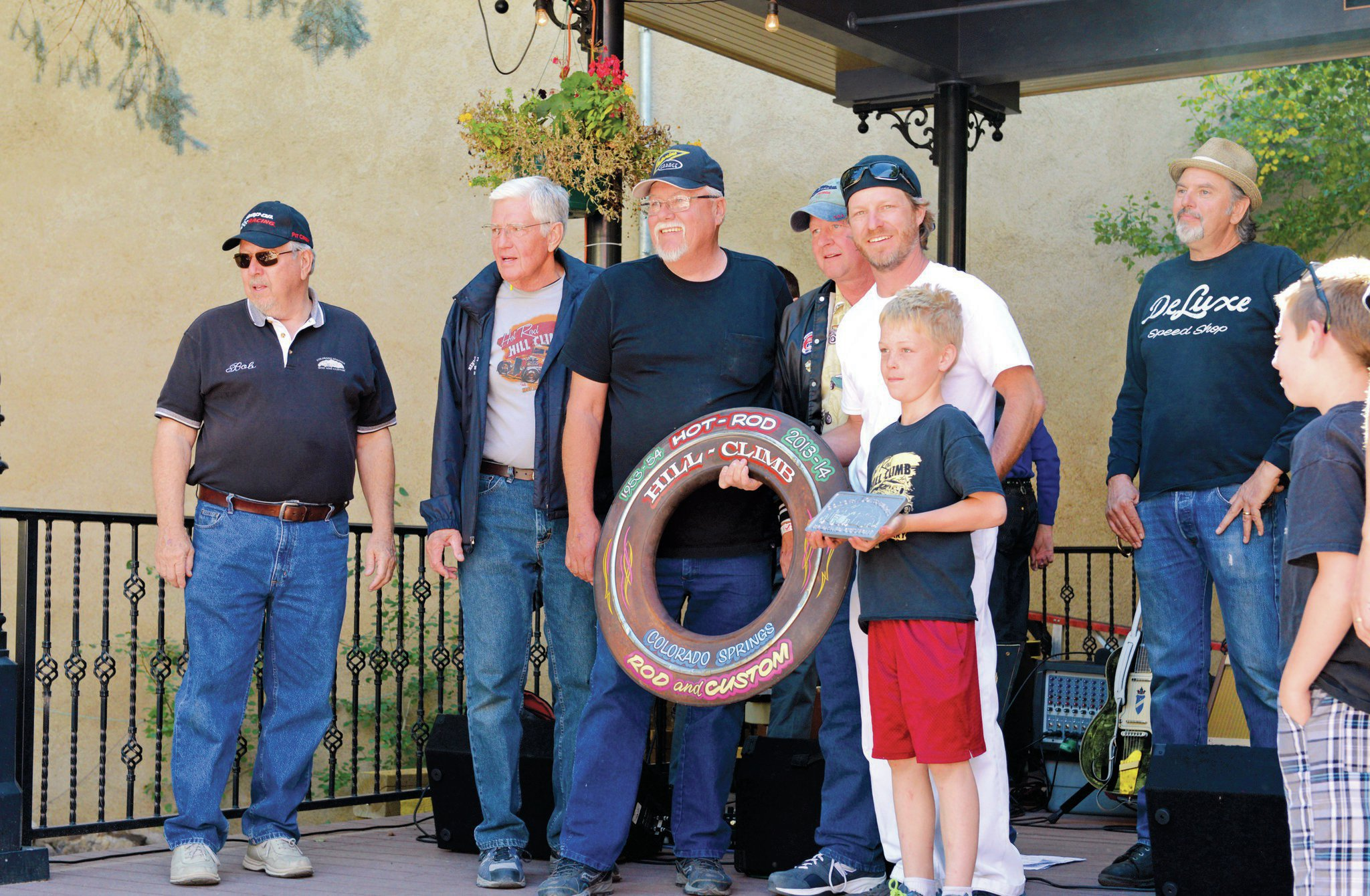 """Members of the Colorado Springs Rod and Custom Car Club present Mike Nicholas with a club plaque and the """"wall art"""" spare tire ring. He was also voted in as an honorary member for his efforts in bringing the HRHC back to Georgetown. From left: Bob Collins, John Mack, Tom Devine, Mike, Mason Nicholas, Scott McCann."""