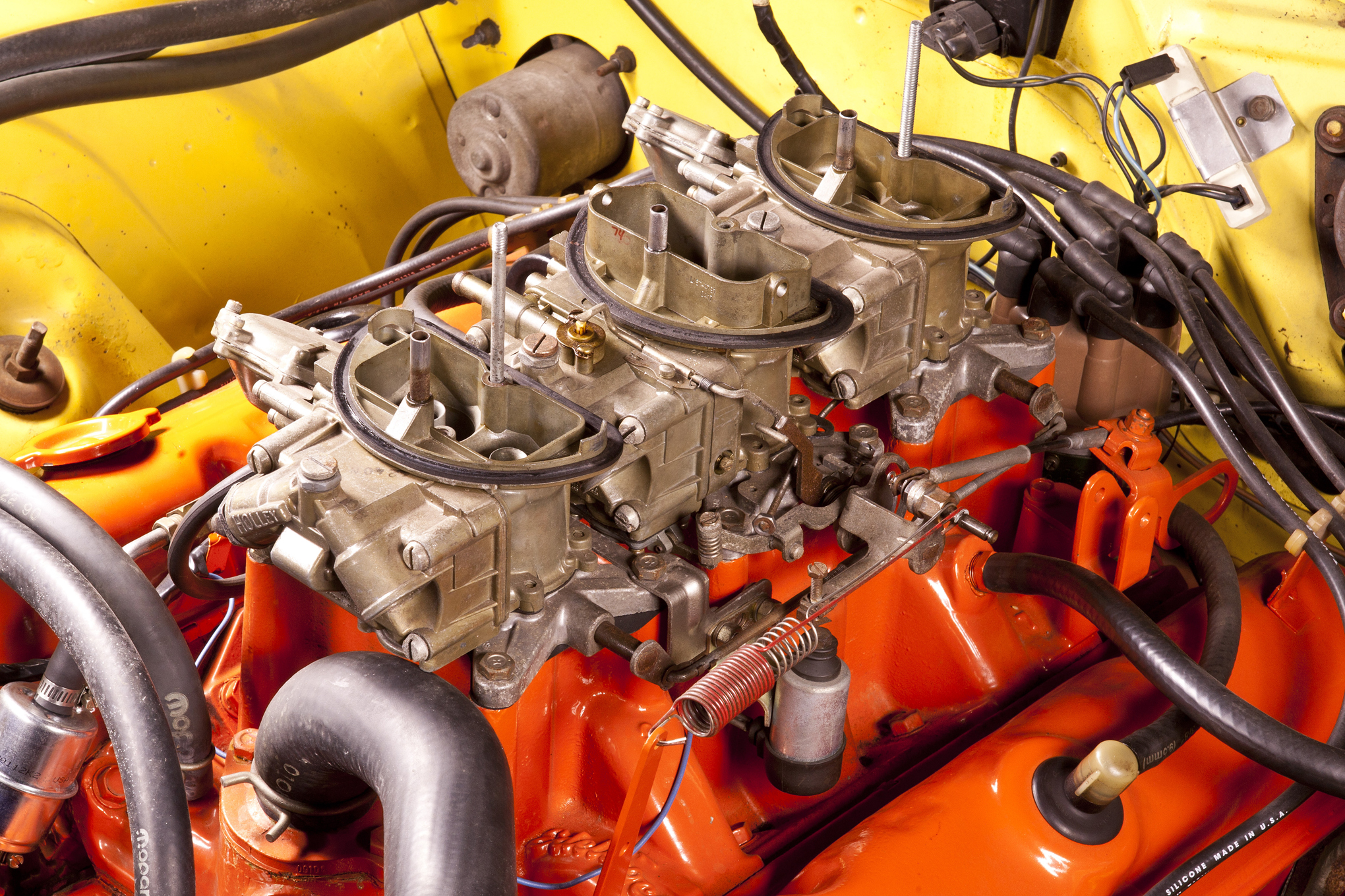 Wide open, the trio of Holley 2300 two-barrels flows 1,350 cfm. The vacuum-actuated end carbs come on gradually to prevent bog. The center carb has 1-1/2-inch throttle plates, smaller than the 1-3/4-inch end plates. Though cast by Edelbrock, Chrysler designed the triple-carb 340 intake manifold.