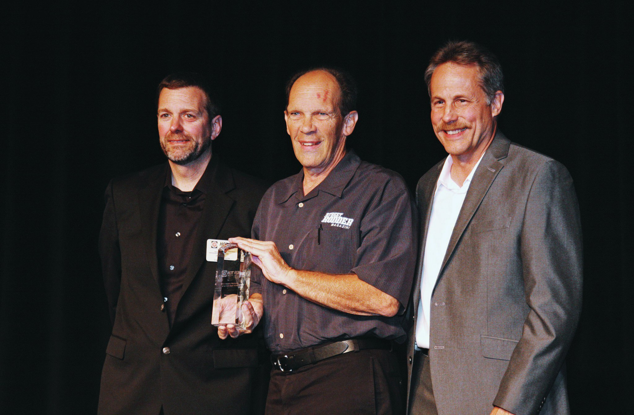 STREET RODDER Editor Brian Brennan (center) receives the 2014 HRIA Industry Recognition Award from HRIA officers John McLeod and Rick Love.