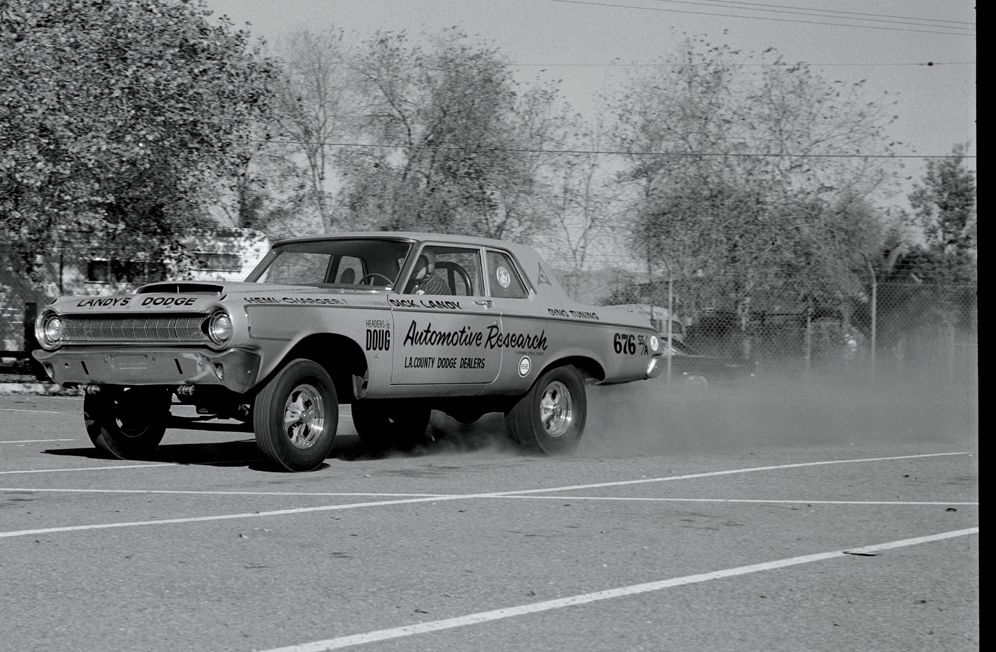 """One of the last film rolls that Eric Rickman exposed this year actually does reveal an early Funny Car. In fact, some folks insist that the relocated axles under Dick Landy's converted S/S and A/MP '64 Dodge qualify this as the first Funny. Guided by blueprints from factory Ramchargers engineers, Landy's Automotive Research finished the job in time to cash in on lucrative late-season match races in the Southeast. Back home in November, Dandy Dick clocked 146.57 (!) mph and won Top Production Eliminator at the same Riverside half-mile meet that produced the preceding Burke & Chastain photo. In mid-December, Rick captured what's likely this car's last burnout, ever, in a San Fernando Valley parking lot. Within weeks, it would be replaced by one of the dozen """"funny-looking"""" '65 Mopars that revolutionized drag racing—as we'll see in the next installment of this series (May '15 HRD)."""