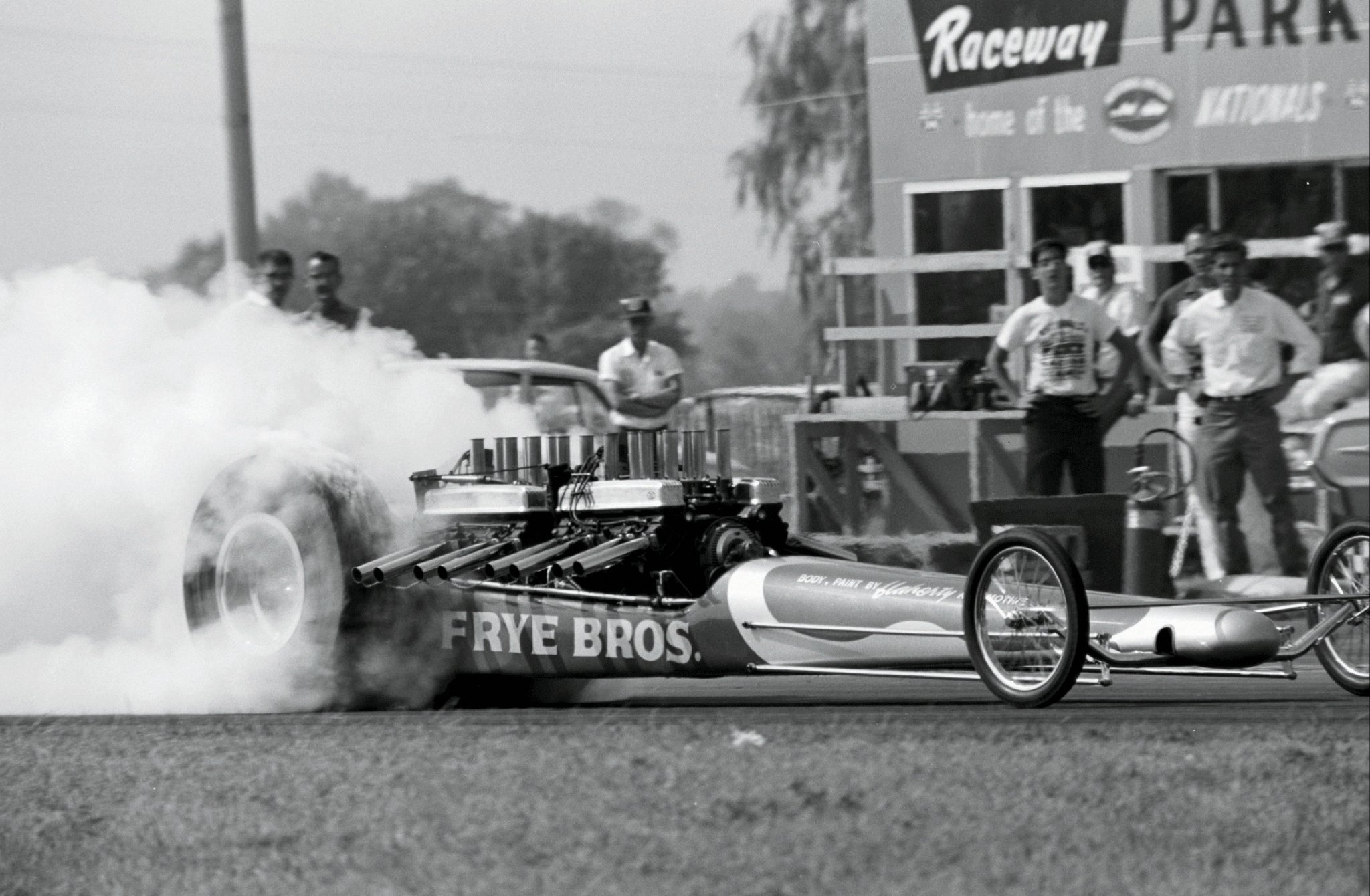 """NHRA's first-ever open fuel show inspired some dual-engined teams to tip the can to their gasoline combinations. Hellacious tire smoke indicates that the Frye brothers' twin Buicks took an immediate liking to """"liquid horsepower"""" at Indy, though we wonder how long their nailheads survived after the shutter was snapped. The crowd-pleasing combination failed to qualify for a Top Fuel field ultimately topped by Don Garlits."""