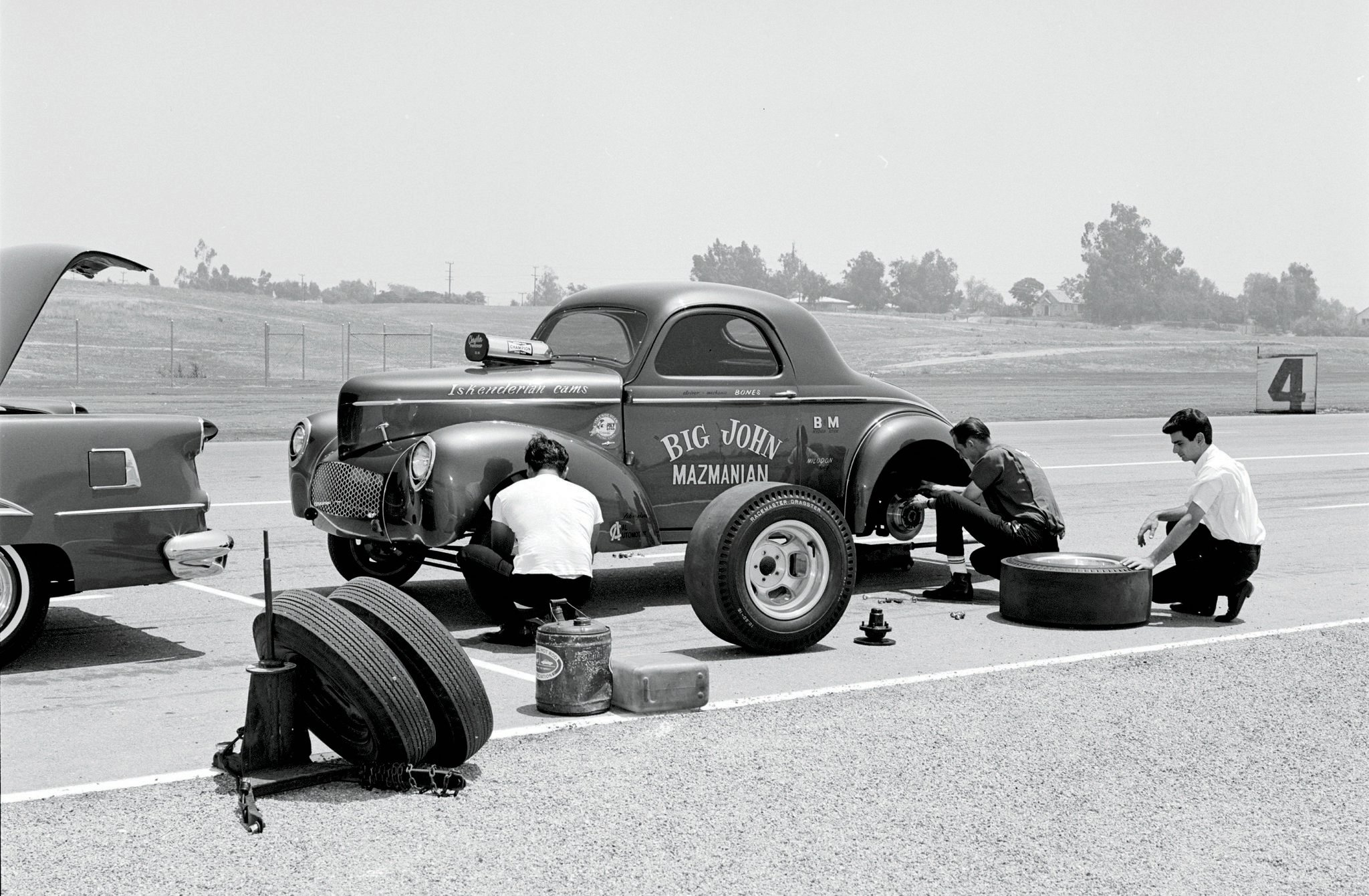 Yes, even the fastest door-slammers were typically flat-towed in 1964. Shown swapping out John Mazmanian's treaded rear tires (foreground) on RIR's Turn Four are current and future pilots Bones Balough (at rear fender) and Richard Siroonian (far right), Big John's nephew. The team earned both the A/GS and Best Appearing Car trophies at the HOT ROD meet.