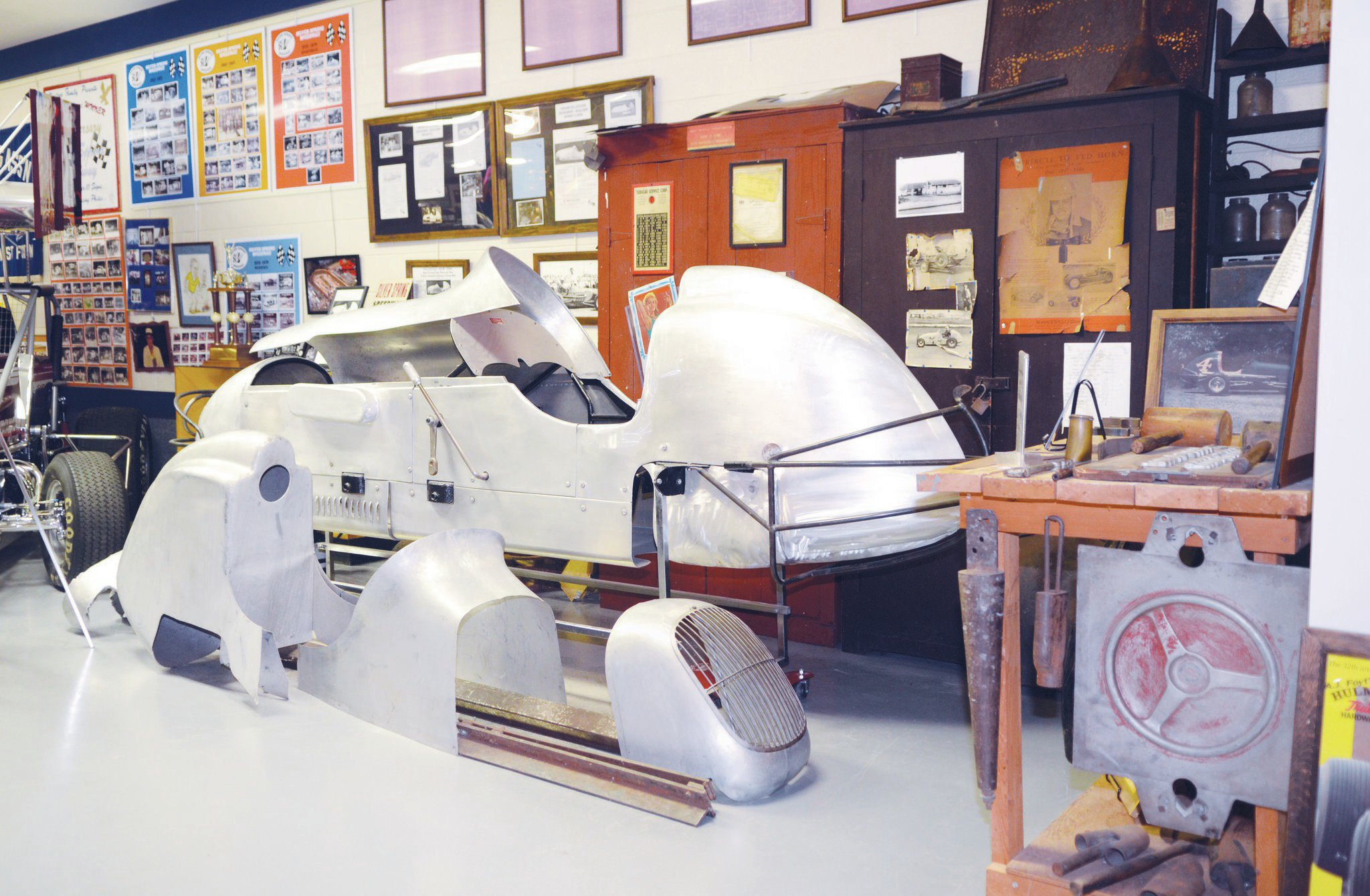 This display highlights a set of tools, hammer forms, and an under-construction roadster body. It is one of several life-size diorama-type layouts in the EMMR's multiple halls.