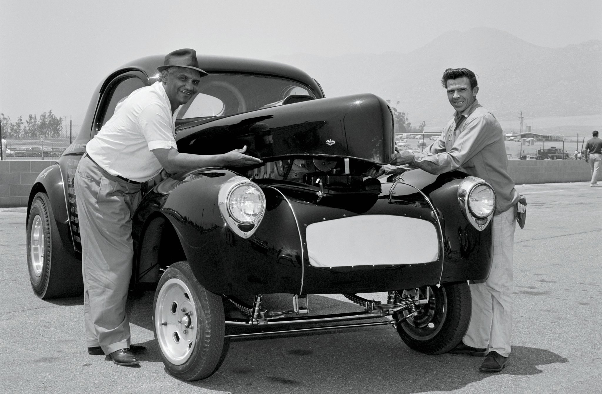 Tim Woods (left), Doug Cook (right), and Fred Stone campaigned three Super Gassers in '64: this Swindler A, the blue Swindler B, and the Dark Horse '33 Willys driven by Chuck Finders. In the background is Riverside International Raceway, where Car Craft shot a feature during sister-magazine HRM's meet.
